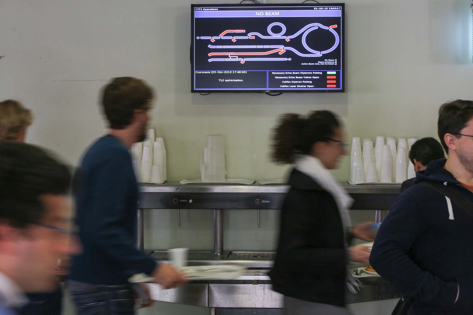 Inside the lunchroom and cafeteria at the CERN, a screen shows live informations about current LHC beam studies