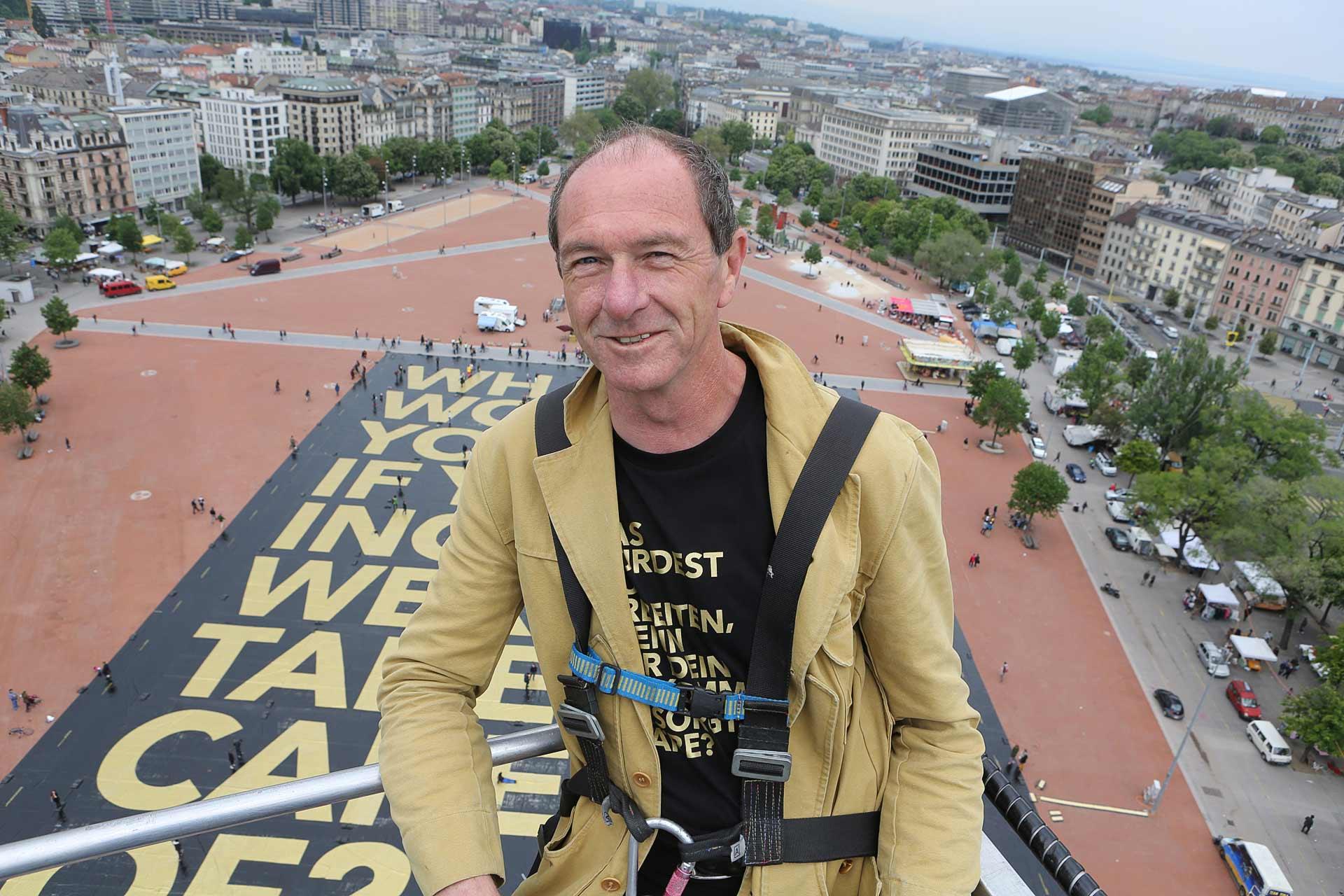 """Enno Schmidt hoch über der Stadt Genf, nachdem der Guinness-Buch-Rekord für das größte Plakat der Welt gewonnen wurde -  """"Bedingungslosigkeit ist weder radikal noch spektakulär"""" taz. die tageszeitung vom 15.10.2009"""