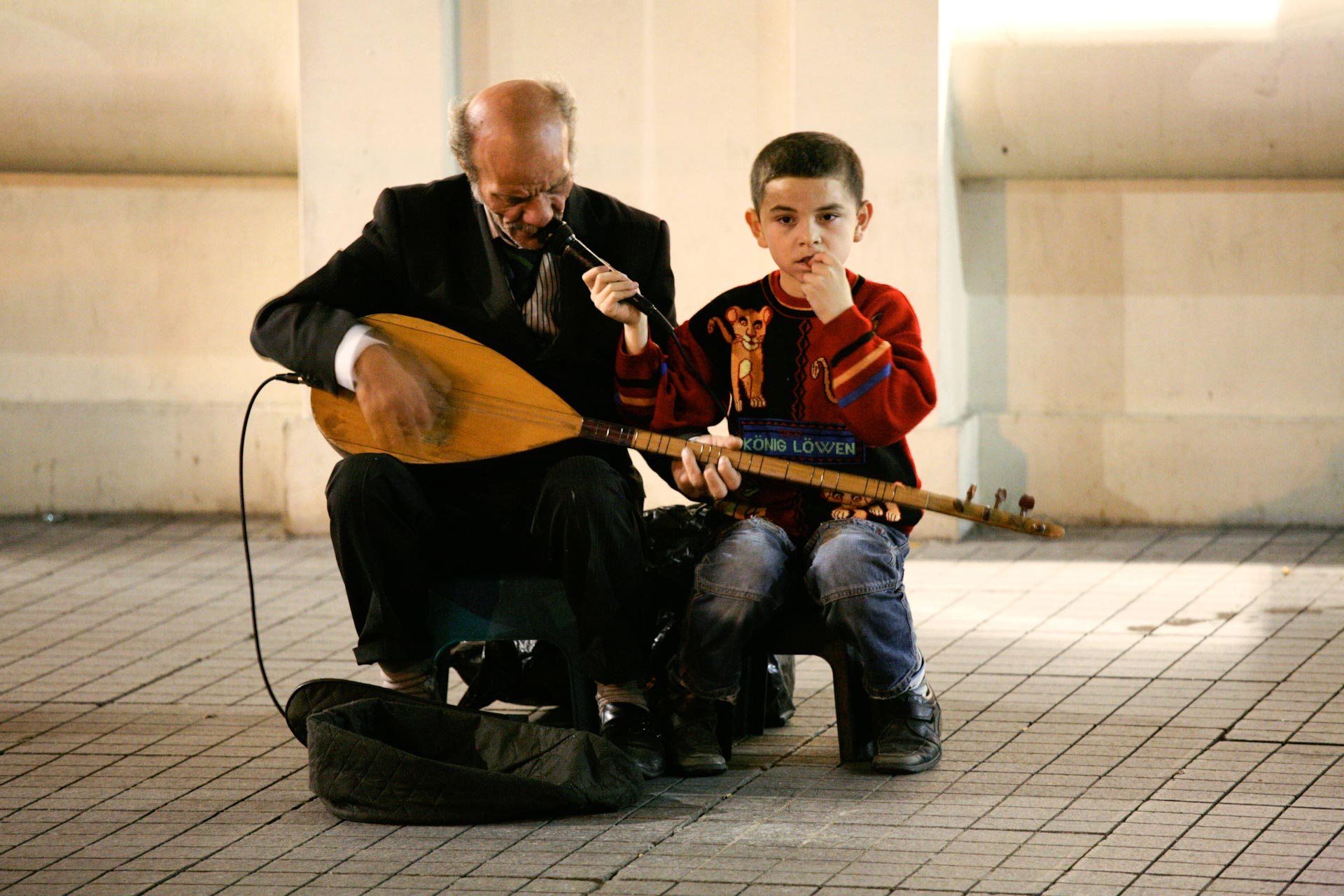 This blind man playing his Saz often on the İstiklal Caddesi, Beyoğlu, beeing assisted by his grandson, who later collects the coins