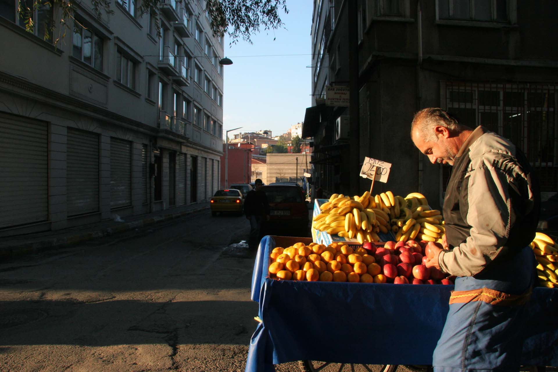 Street merchant polishing his fruits on the street of Tarlabaşı