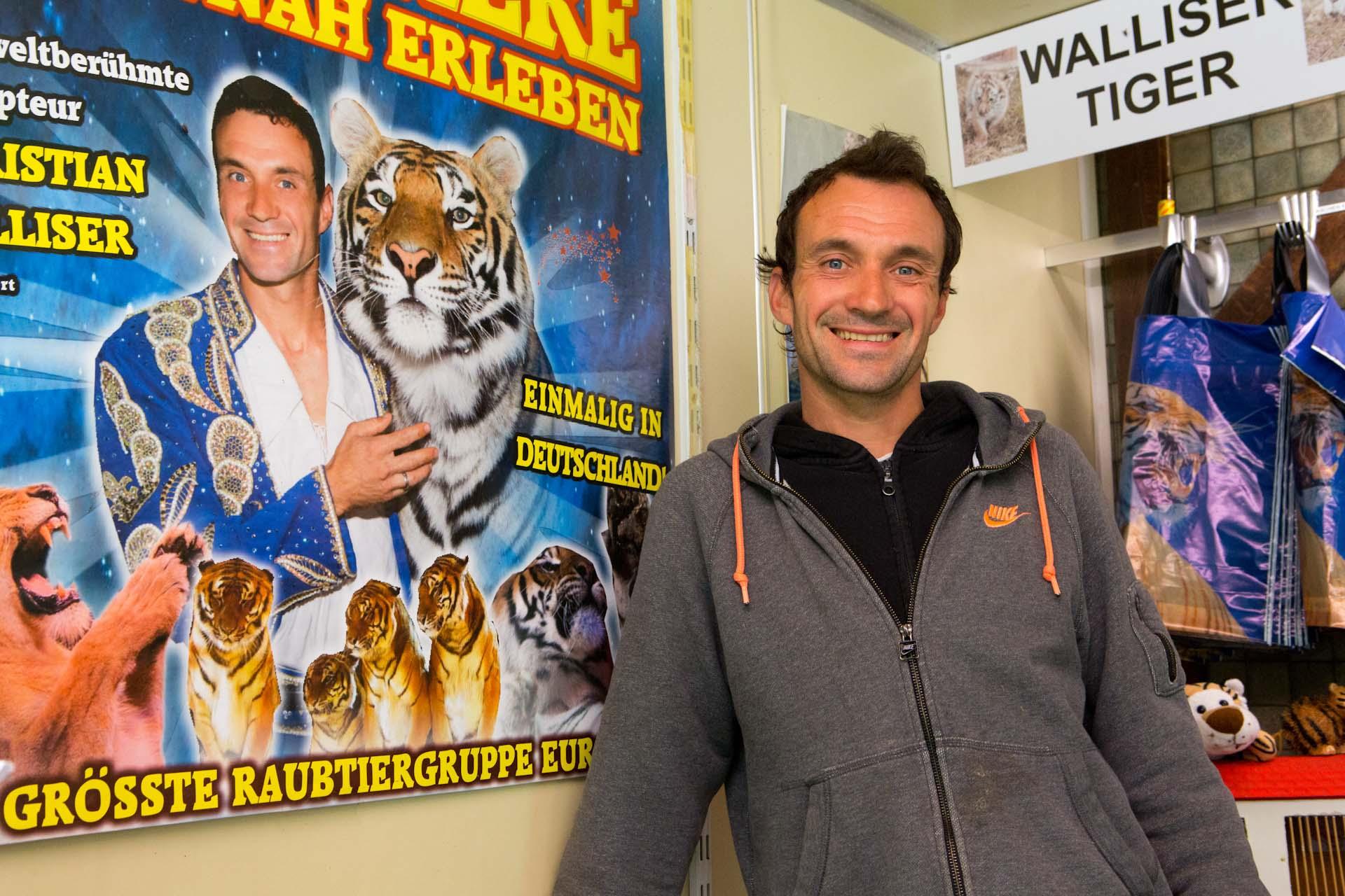 """Christian Walliser im Verkaufswagen des Raubtierhofes. """"Raubtiere hautnah erleben"""" steht auf einem Plakat. Las Vegas im Schwarzwald."""