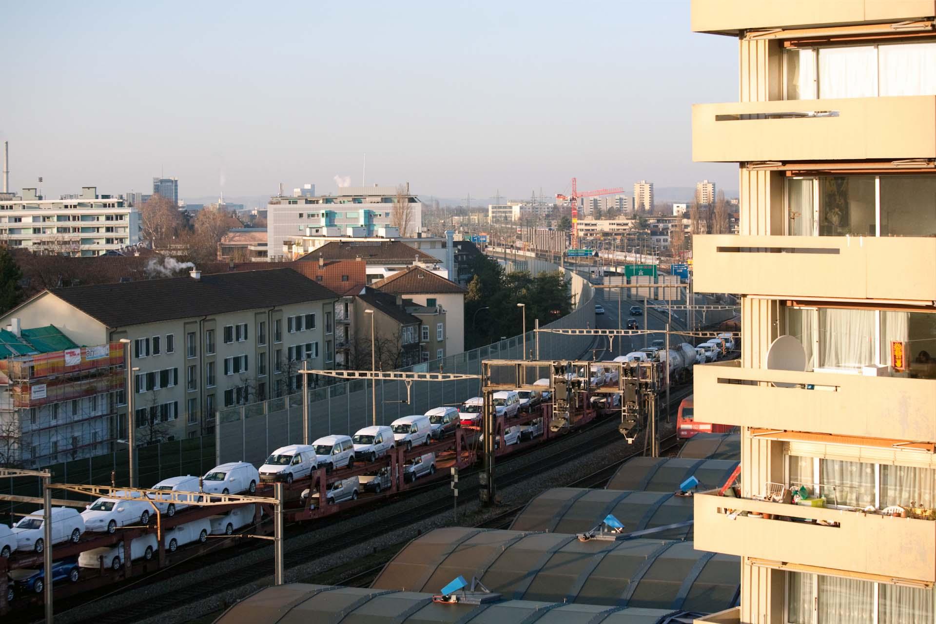 """""""Durch das Panoramafenster seines Wohnzimmers überblickt er ganz Basel. Unten rauscht die Autobahn Richtung Deutschland, daneben auf den Schienen fahren die ICEs nach Amsterdam, Paris, Prag."""""""