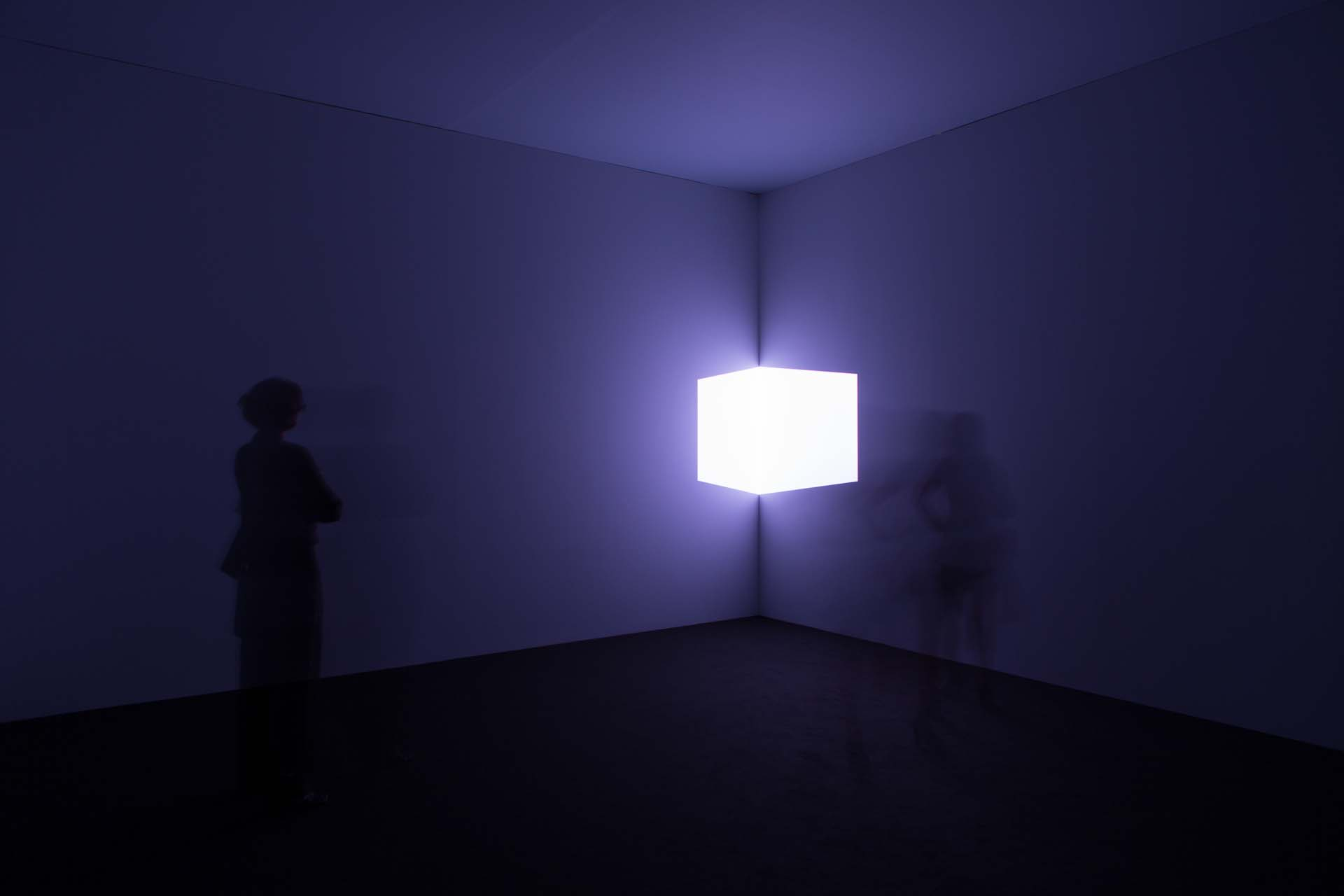 "Art Unlimited 2018: James Turrel, Catso Violet, 1967 – ""James Turrell designed Catso Violet in 1967, as part of the 'Cross Corner Projections' series. In this work, the artist created what appears to be a blue violet cube mounted in a corner of a specific space, free-floating, its source of light from a projection diagonally across the room. From a distance the shape has solidity but it is literally composed of nothing other than light. Advancing towards the work, the image eventually dissolves to the point where the viewer sees not the object, but the actual light on the wall. This piece objectifies and transforms our perceptions of light into a physically tangible material."""