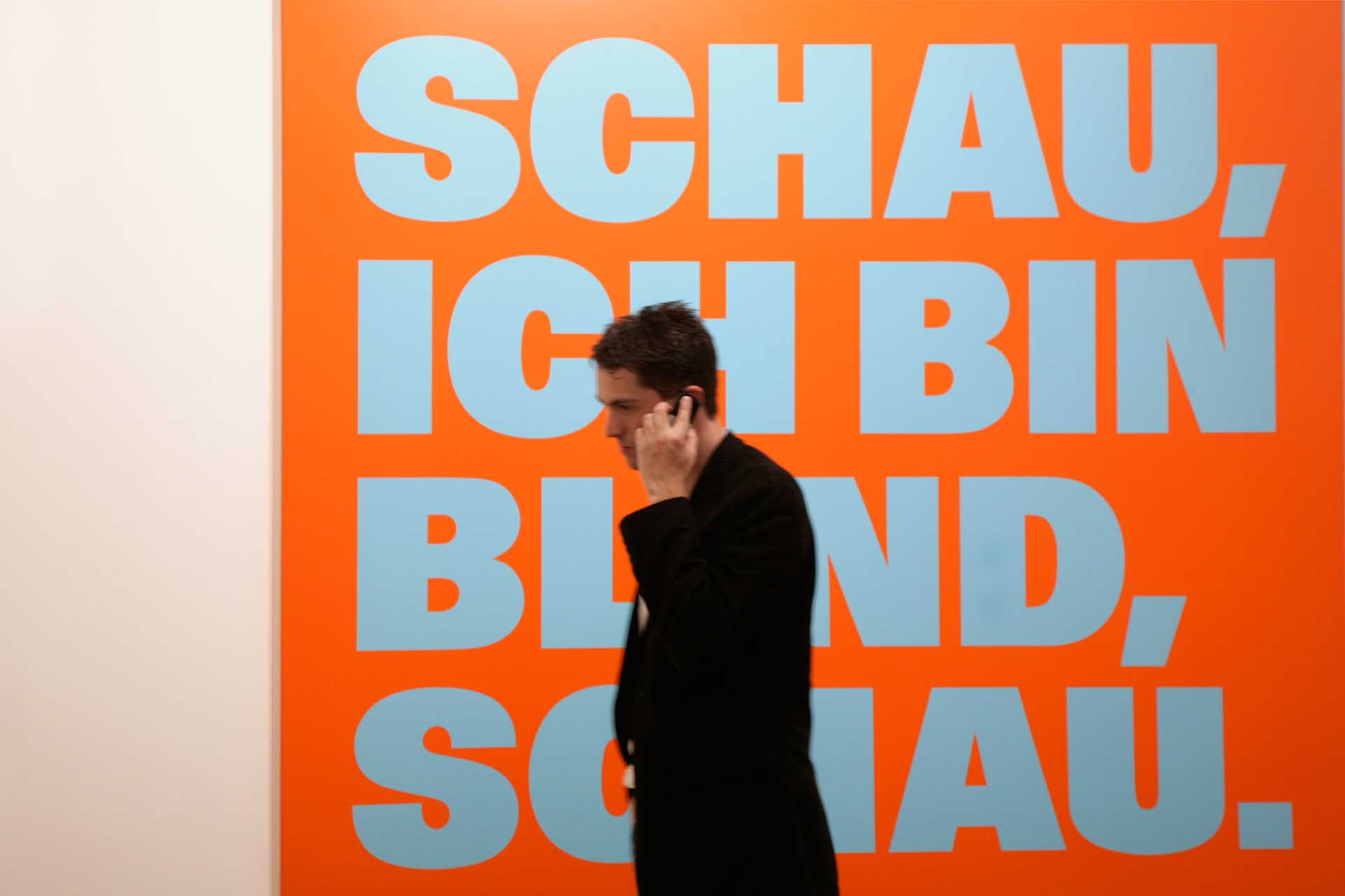 "A visitor to the Art 41 vernissage in Basel strolls past a work phoning: ""SCHAU, ICH BIN BLIND, SCHAU"" 98/99, by the Swiss painter and concept artist Remy Zaugg, 2010"