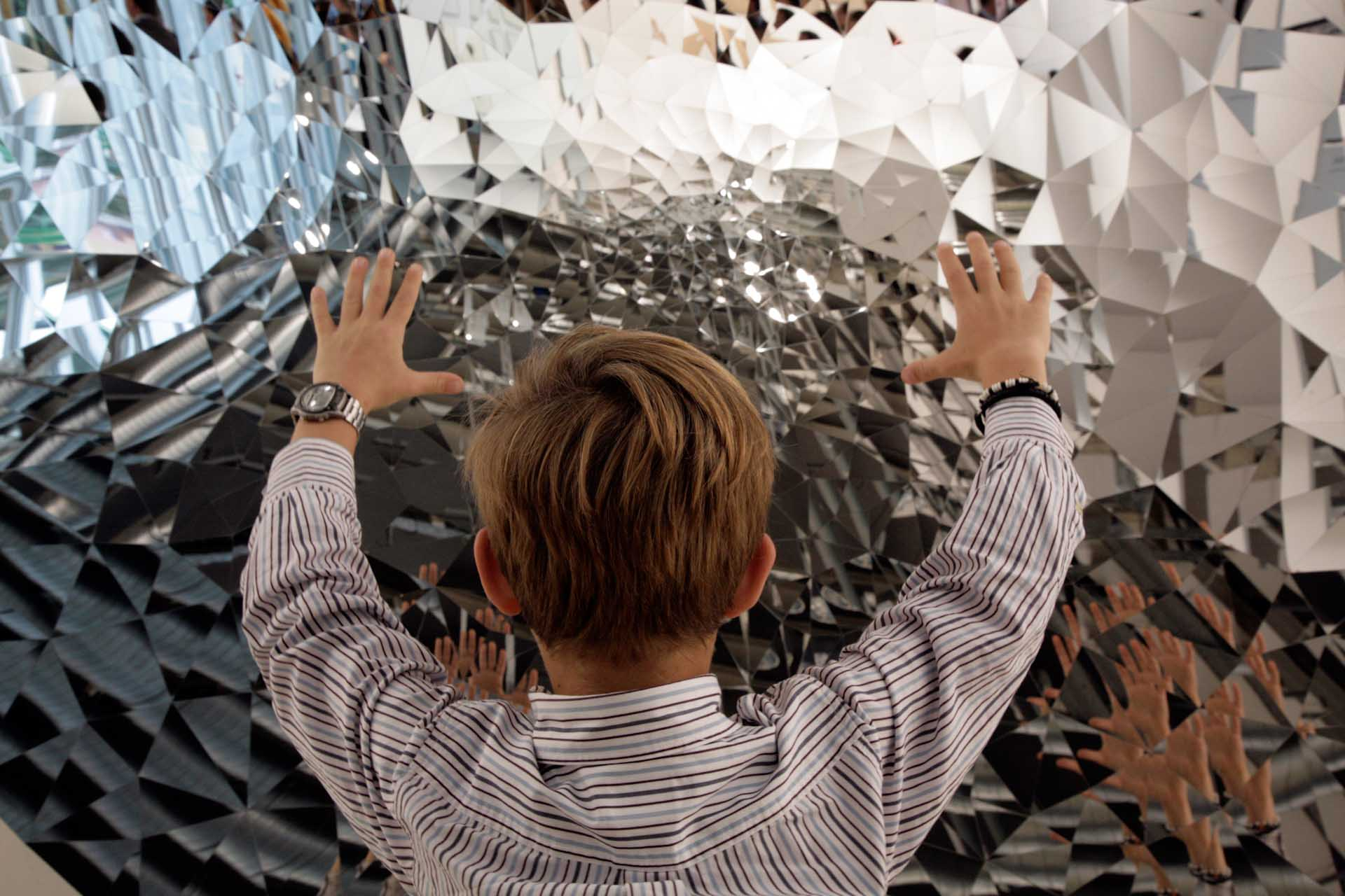 Art 40, 2009: Boy looks at his 100 faces in a kinetic object by Anish Kapoor