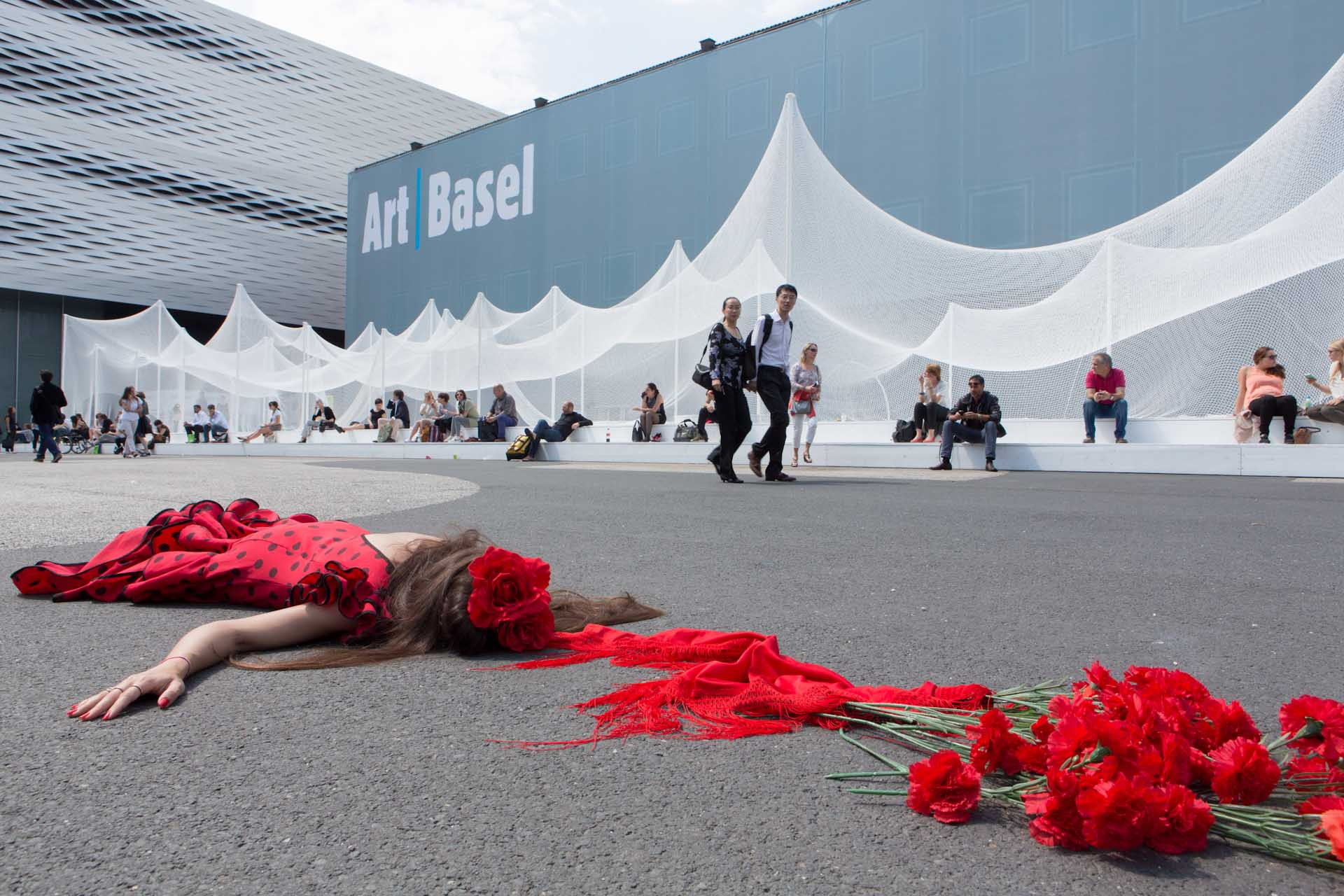 "View of the Art Basel exhibition square, with the walk-in installation ""Zerzura"" under the label ""Panterapantera"", 2014, by architects Jens Müller & Thomas Wüthrich. In the foreground a woman in red dress, who makes a private live performance independent of Art Basel, 2014"
