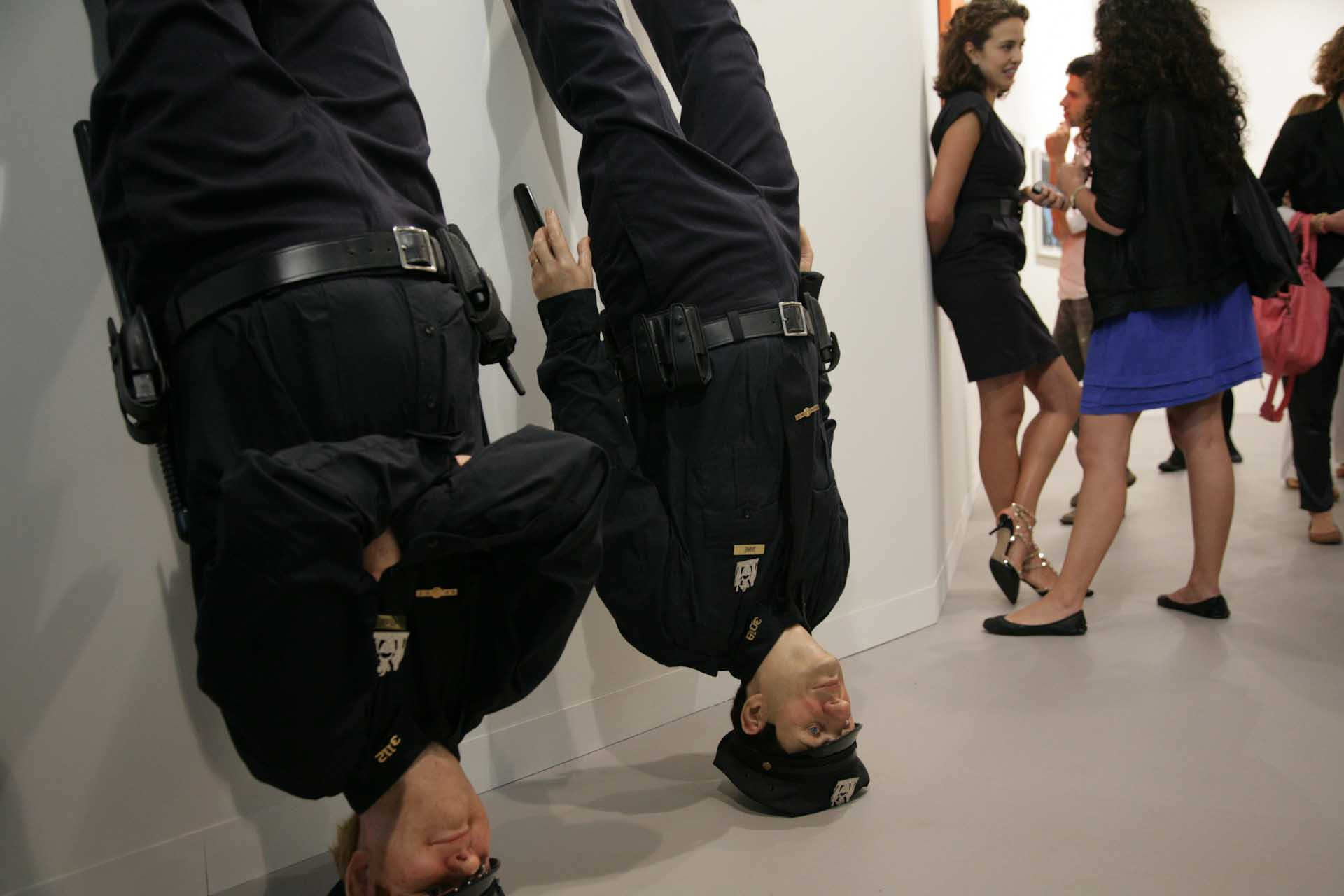 "Art 42, 2011: Two inverted cops, the sculpture ""Frank and Jamie"" (2002) by Maurizio Cattelan"