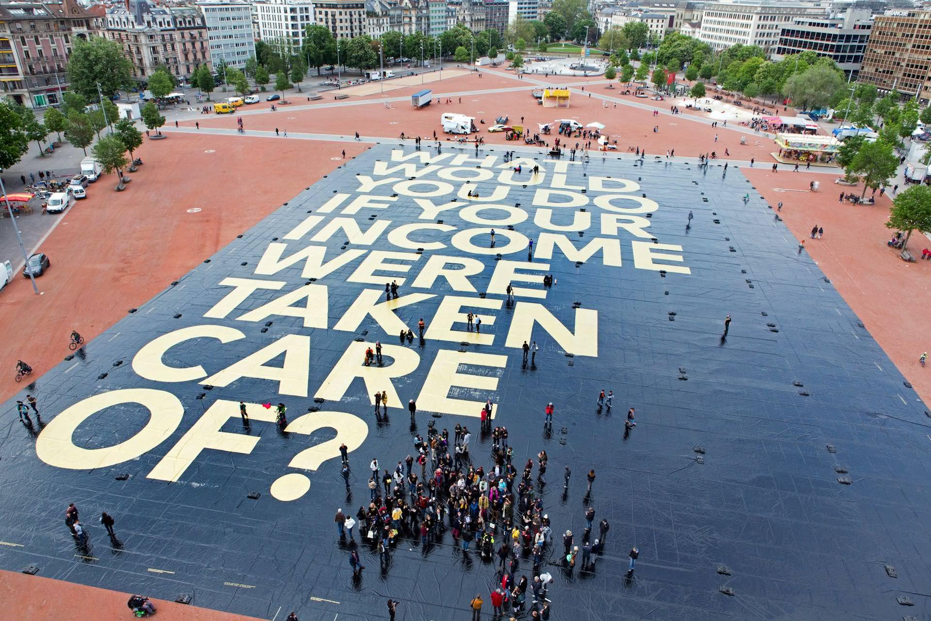 """Und nochmal besticht die Kampagne durch ihre Kreativität: Eine der Aktionen hat es ins """"Guinness-Buch der Rekorde"""" geschafft. Die Frage """"Was würdest du arbeiten, wenn für dein Einkommen gesorgt wäre?"""" wurde in Genf auf ein 8.115,53 Quadratmeter großes Plakat gedruckt und ist damit das größte Plakat der Welt. Das macht das junge Kampagnenteam aus. Ästhetik, Großzügigkeit, überraschende Bilder, kein Dagegen."""