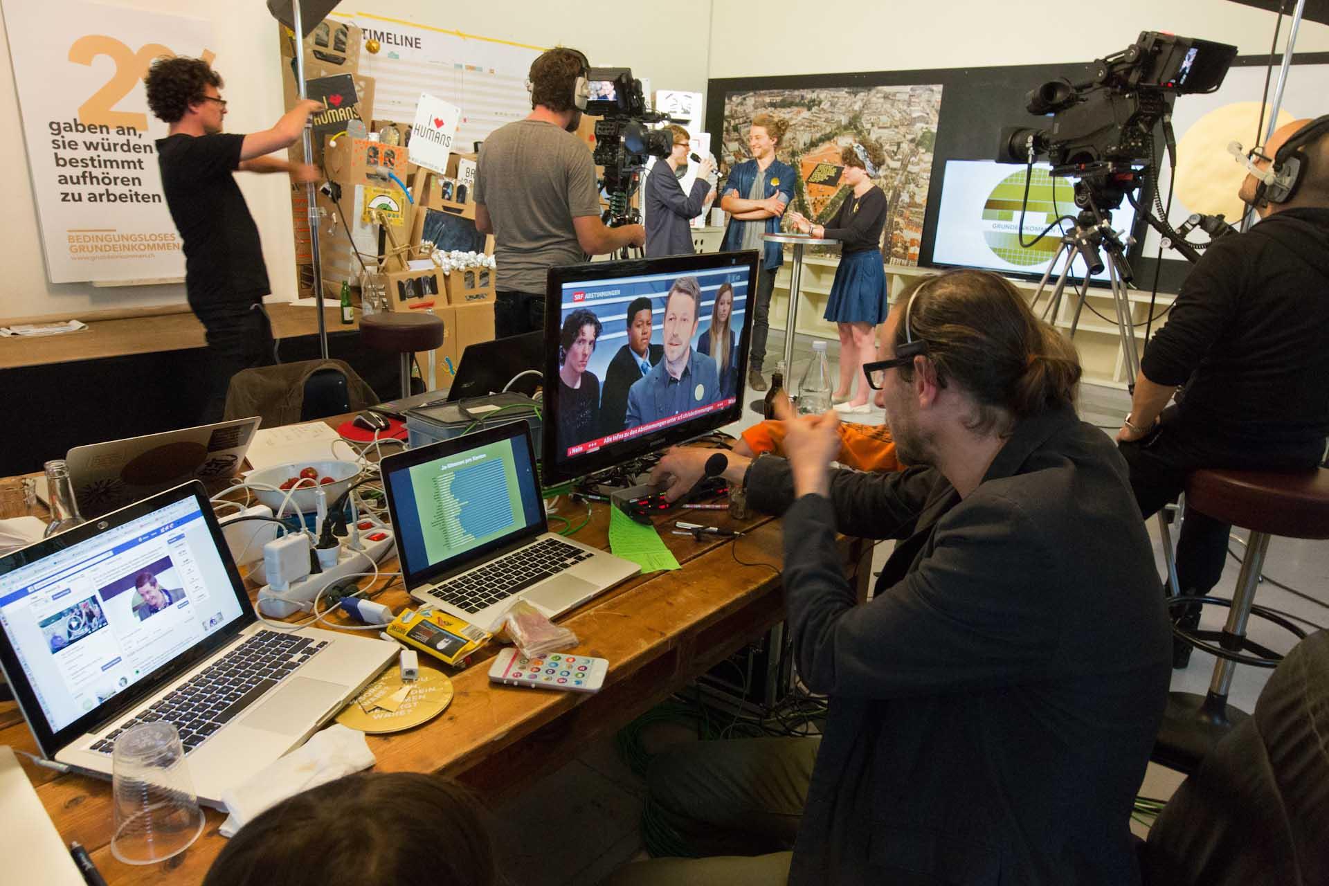 """Zur Abstimmung wurde im """"unternehmen mitte' ein temporäres Fernsehstudio eingerichtet. Daniel Häni sitzt in einer Live-TV-Sendung der SRF und kommentiert die Abstimmung..."""