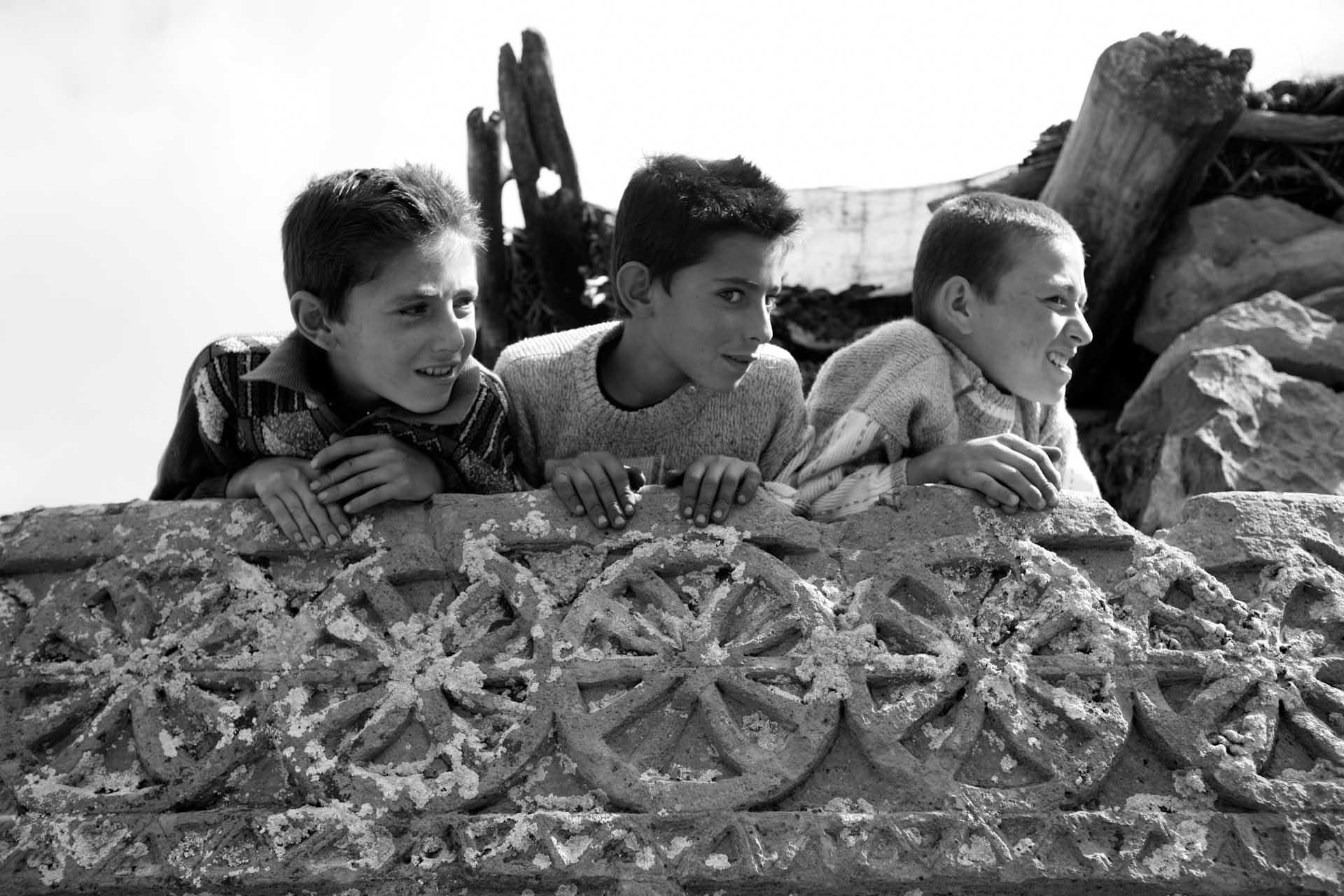 Die kurdischen Jungs können die Bedeutung dieser Stelen noch nicht verstehen, aber sie verstehen sie als eine Attraktion des Dorfes.