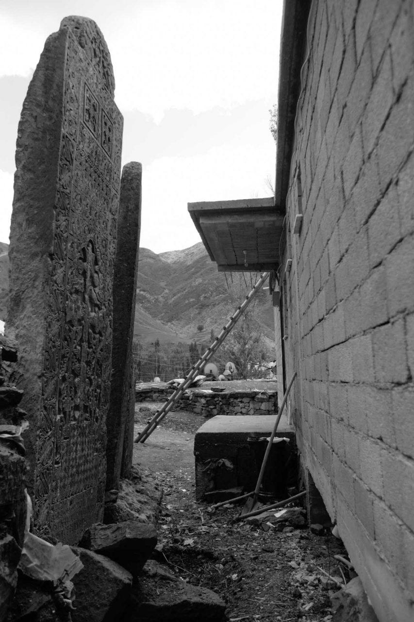 Vor dem Haus stehen drei Khatchkare, von denen einer zerstört ist, alle drei tragen Inschriften in armenischer Sprache.