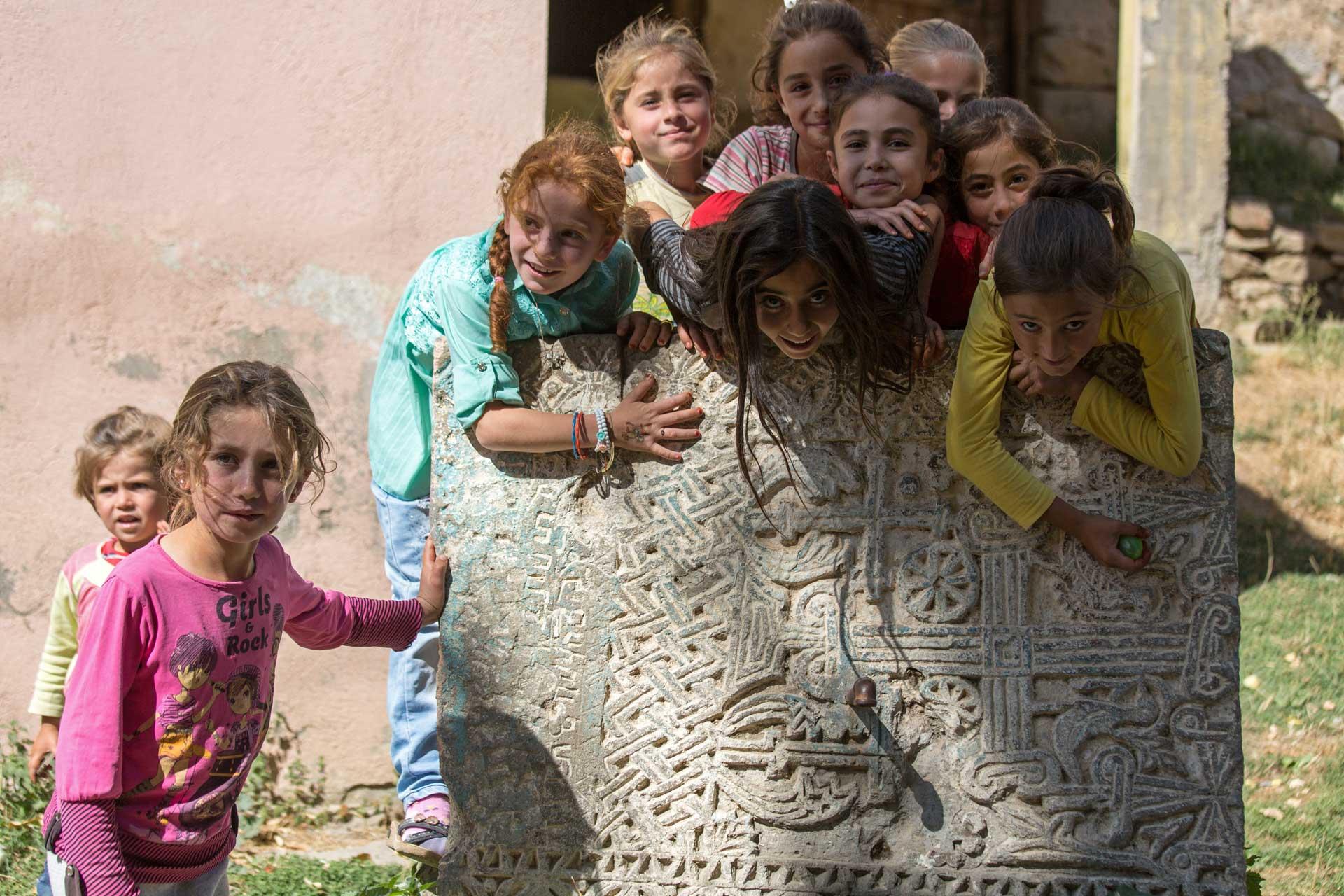 Die Dorfmädchen balgen sich für den Fotografen. Die Schönheit dieses Khatchkars wurde immerhin erkannt und man hat ihn in einen schmucken Dorfbrunnen verwandelt.