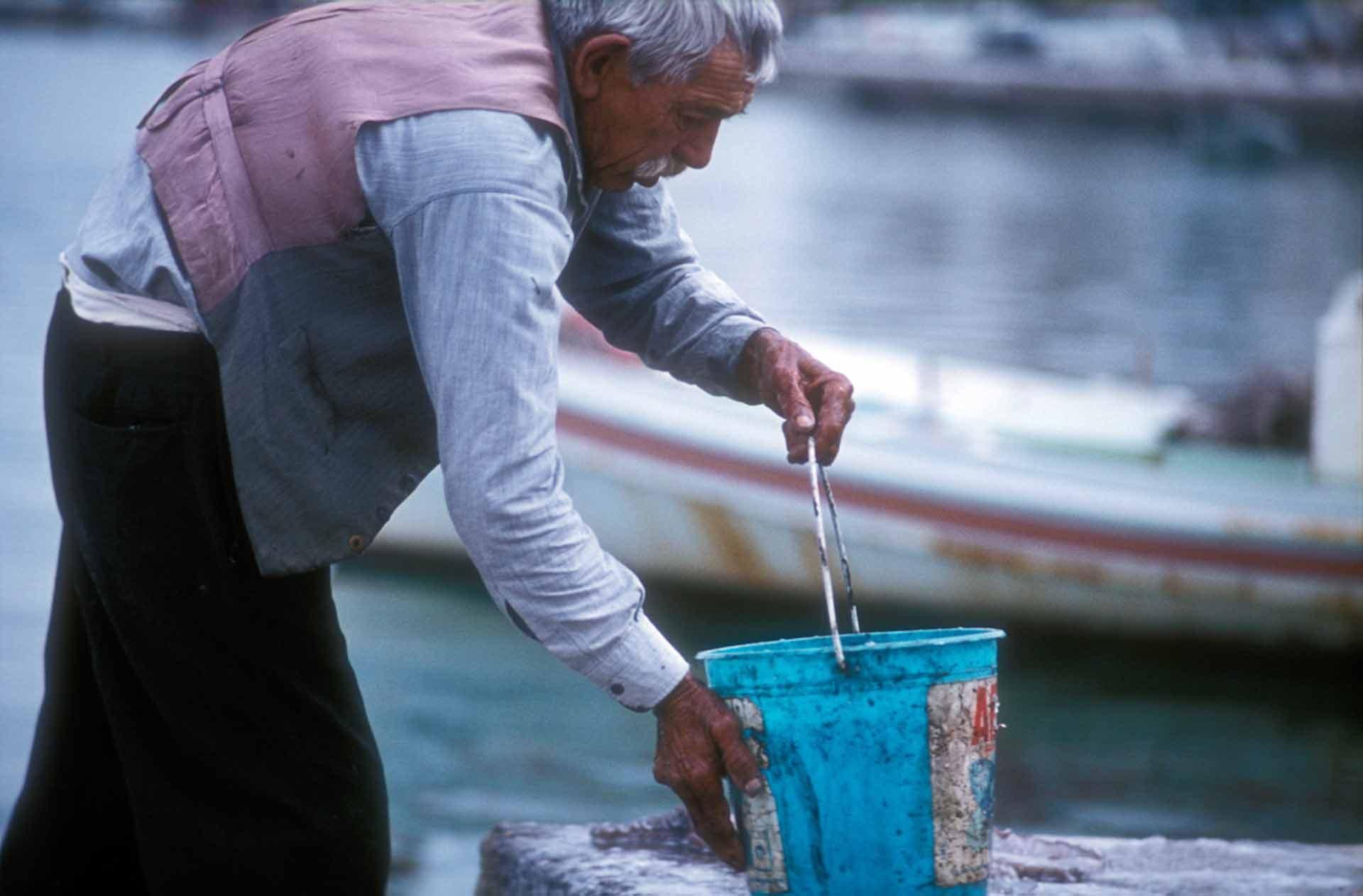 Ein alter Fischer wäscht einen Tintenfisch