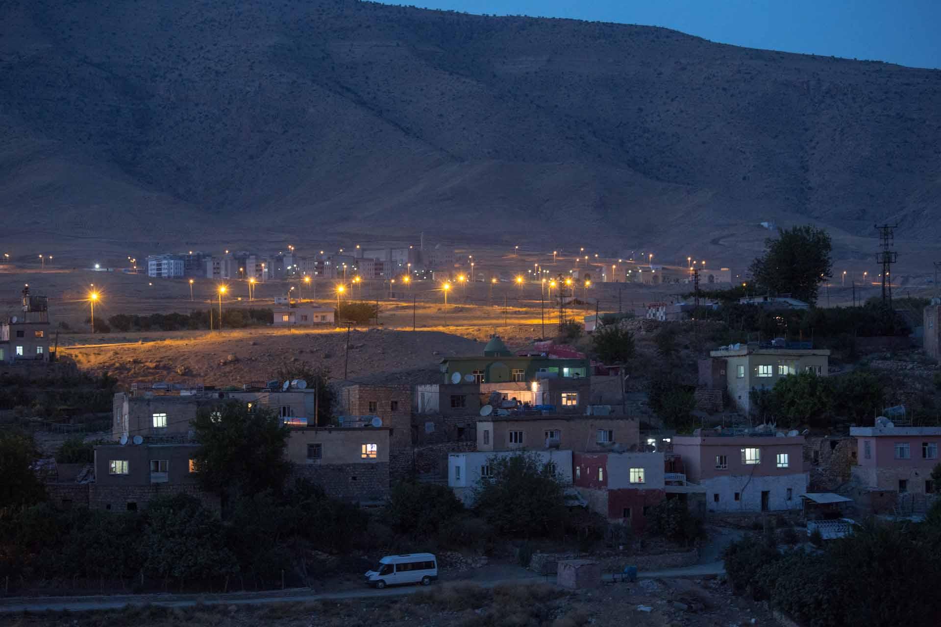 Am Berghang, hinter den abendlich beleuchteten Häusern des Ortes, das neue erbaut Yeni-Hasankeyf, Neu-Hasankeyf.