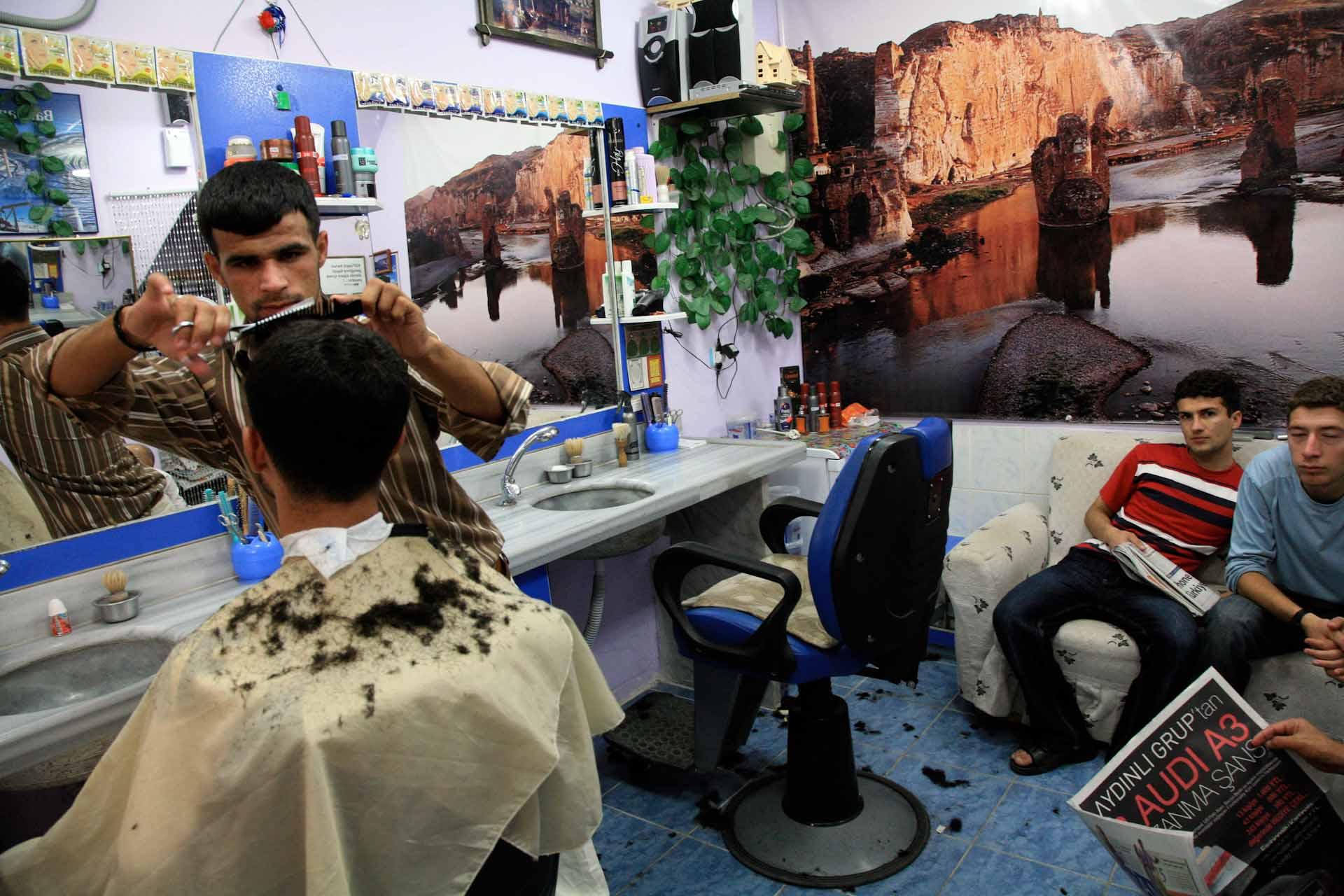 Am Ende der Fastenzeit Ramadan und vor dem höchsten türkischen Feiertag Ramadan haben die Friseure viel zu tun. Der Frisiersalon ist mit Fotos der einzigartigen, mittelalterlichen, durch das Ilisu-Staudamm-Projekt bedrohten Steinbruecke des Ortes geschmückt.