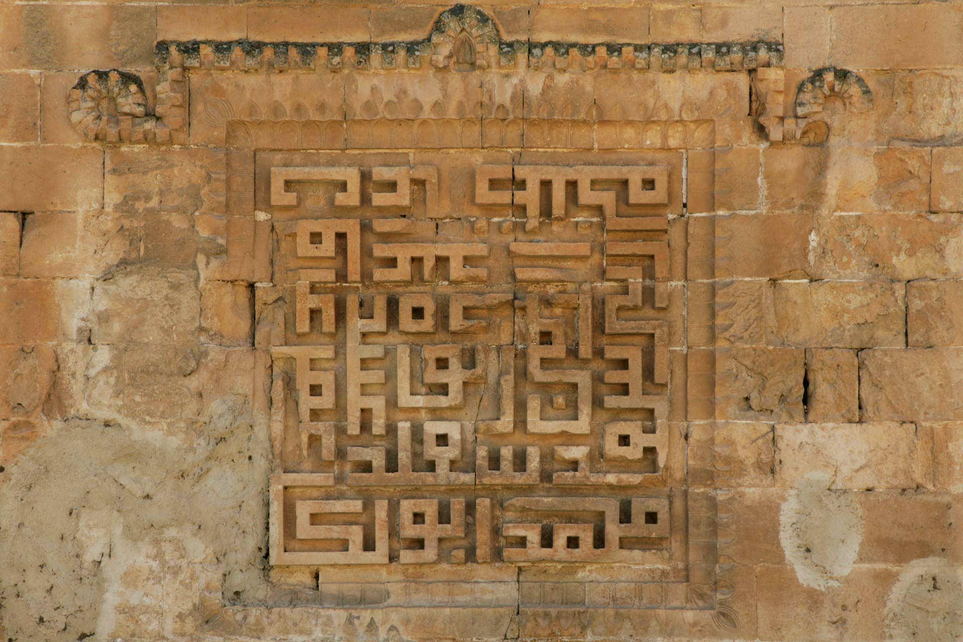 Quadratkufi, hier im Sockel des Minaretts der El-Rizk Moschee, ist eine sehr stark vereinfachte Variante der kufischen Schrift, die in der islamischen Architektur verwendet wurde. Das entstehende geometrische Muster besteht aus Wiederholungen von Namen wie Allah, Mohammed und Ali. Aber auch längere Texte werden manchmal in quadratischem Kufi verfasst und sind oft schwer zu entziffern.