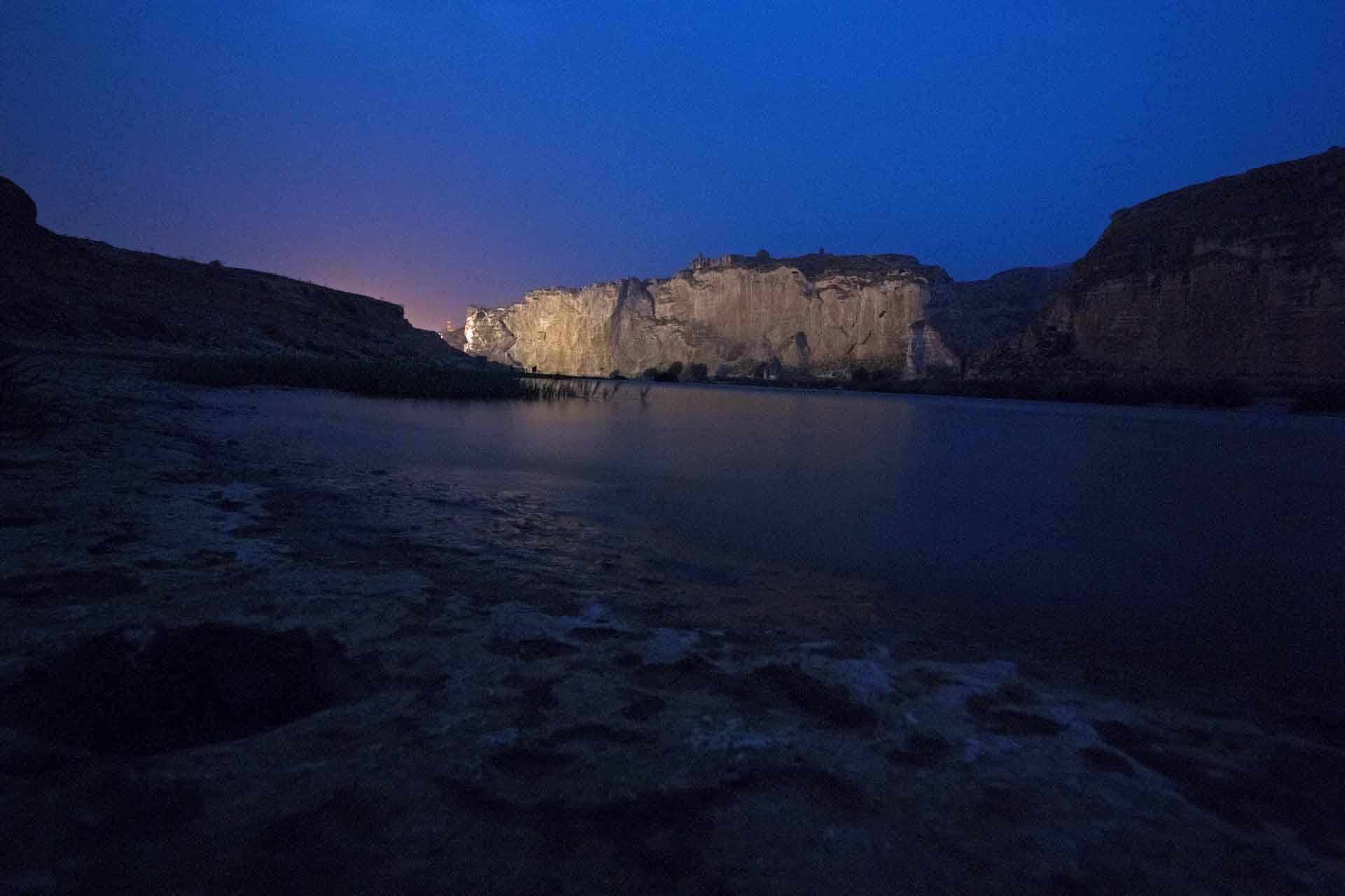 Der Felsen von Hasankeyf bei einbrechender Dunkelheit. Der Felsen wird durch die Baustelle der Brückenpfeiler beleuchtet.