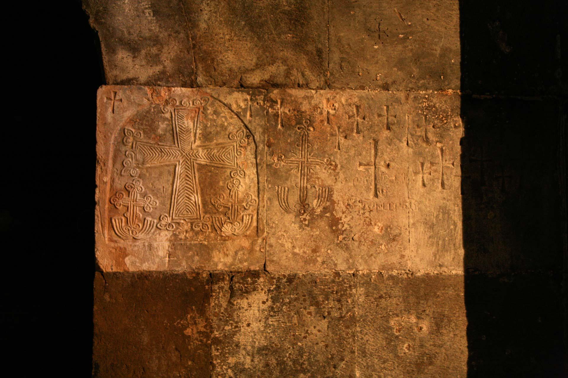 Kreuzzeichnungen auf den Sandsteinmauern des Klosters Varak.