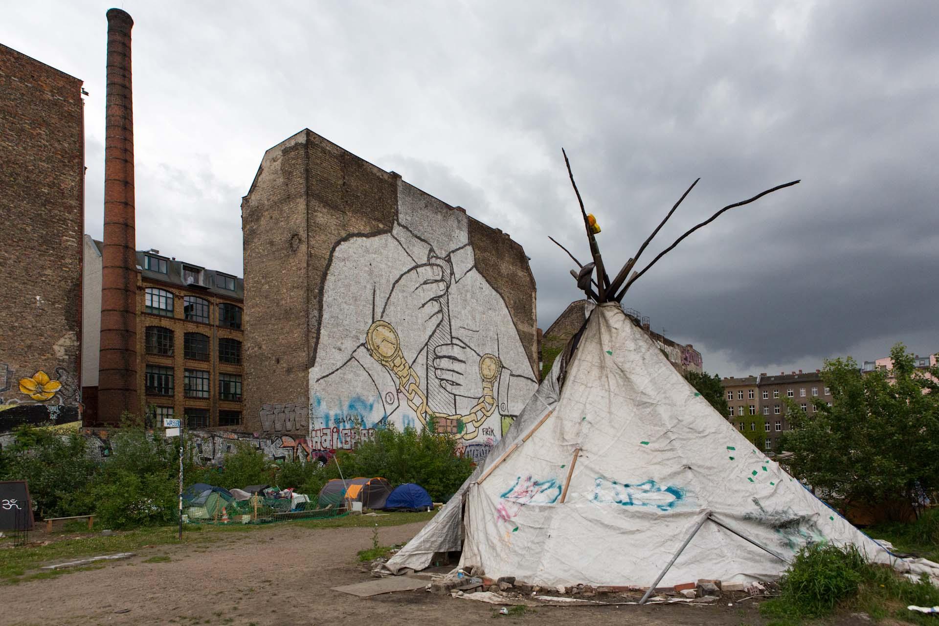 """Bekanntes Graffiti von 'Blu' an der Brandmauer des besetzten Grundstücks an der Cuvrystrasse in Kreuzberg. Bis zur Räumung wohnten viele Menschen in provisorischen Unterkünften in Deutschlands """"einziger Favela"""". Das Vorhaben das Grundstück mit Büroblocks zu überbauen, stagniert momentan, da Zalando als Mieter abgesprungen ist."""