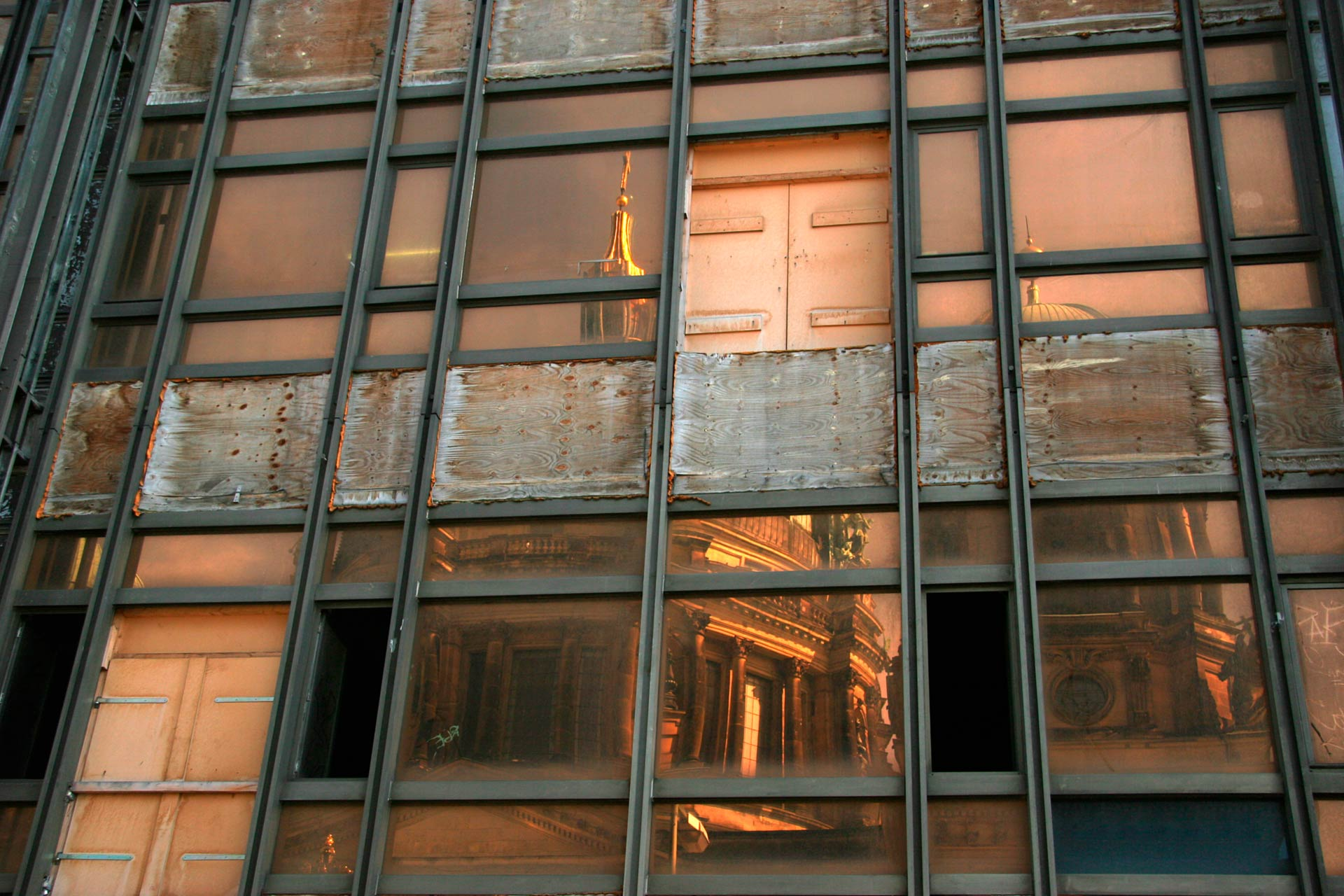 Der Berliner Dom spiegelt sich in der beschädigten Glasfassade des Palastes der Republik.