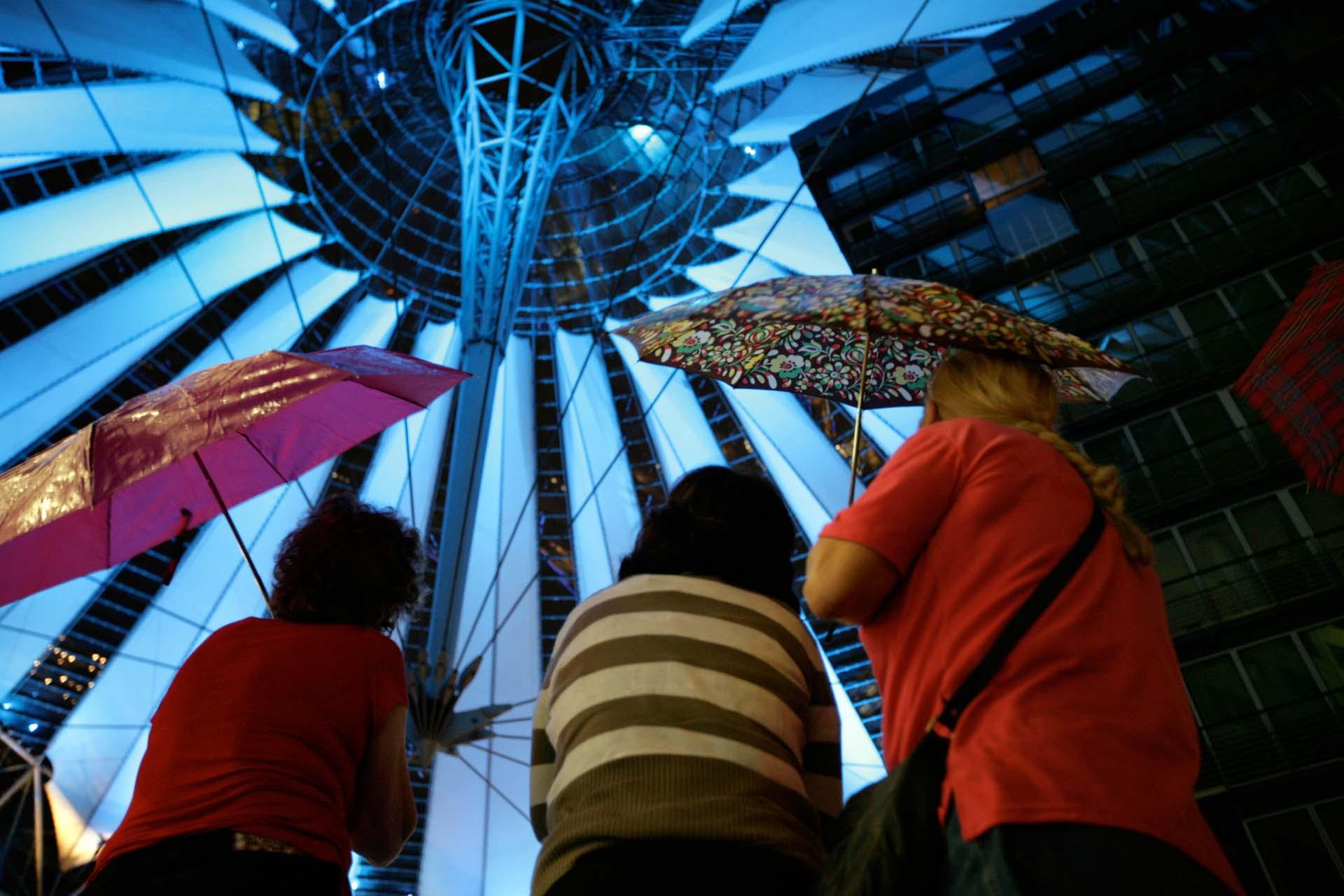 Besucherinnen unter dem großen Regenschirm im Sony-Center am Potsdamer Platz.