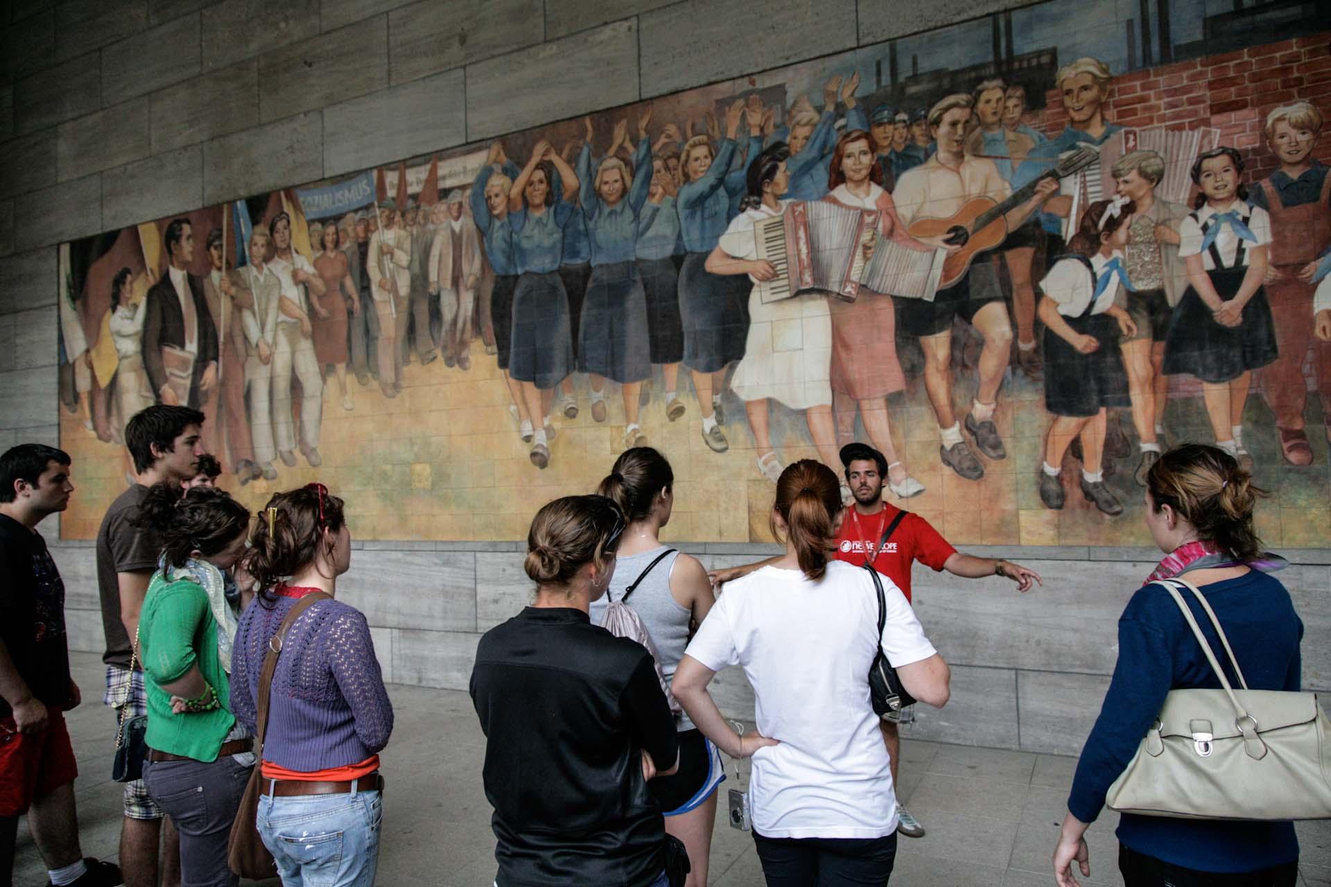 """Ein Guide erklärt ein monumentales sozialistisches Wandbild (1952) von Max Lingner, dessen Kacheln aus Meissener Porzellan gebrannt wurden, am ehemaligen """"Haus der Ministerien"""", dem heutigen Bundesfinanzministerium."""