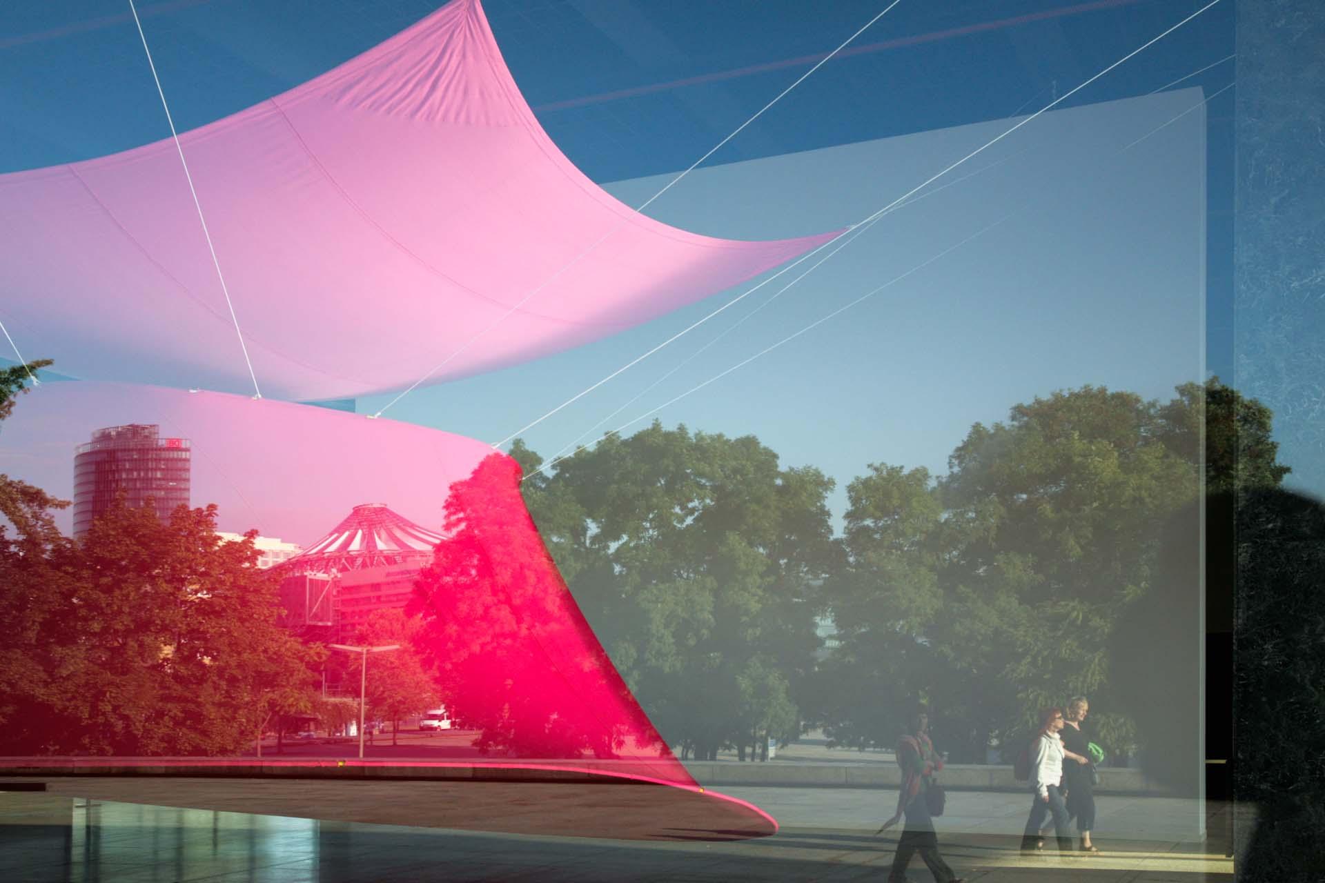 """Im Fenster der Neuen Nationalgalerie Berlin spiegelt sich der Potsdamerplatz mit DB-Tower und Sony Center, sowie Rupprecht Geigers """"Rote Trombe""""."""