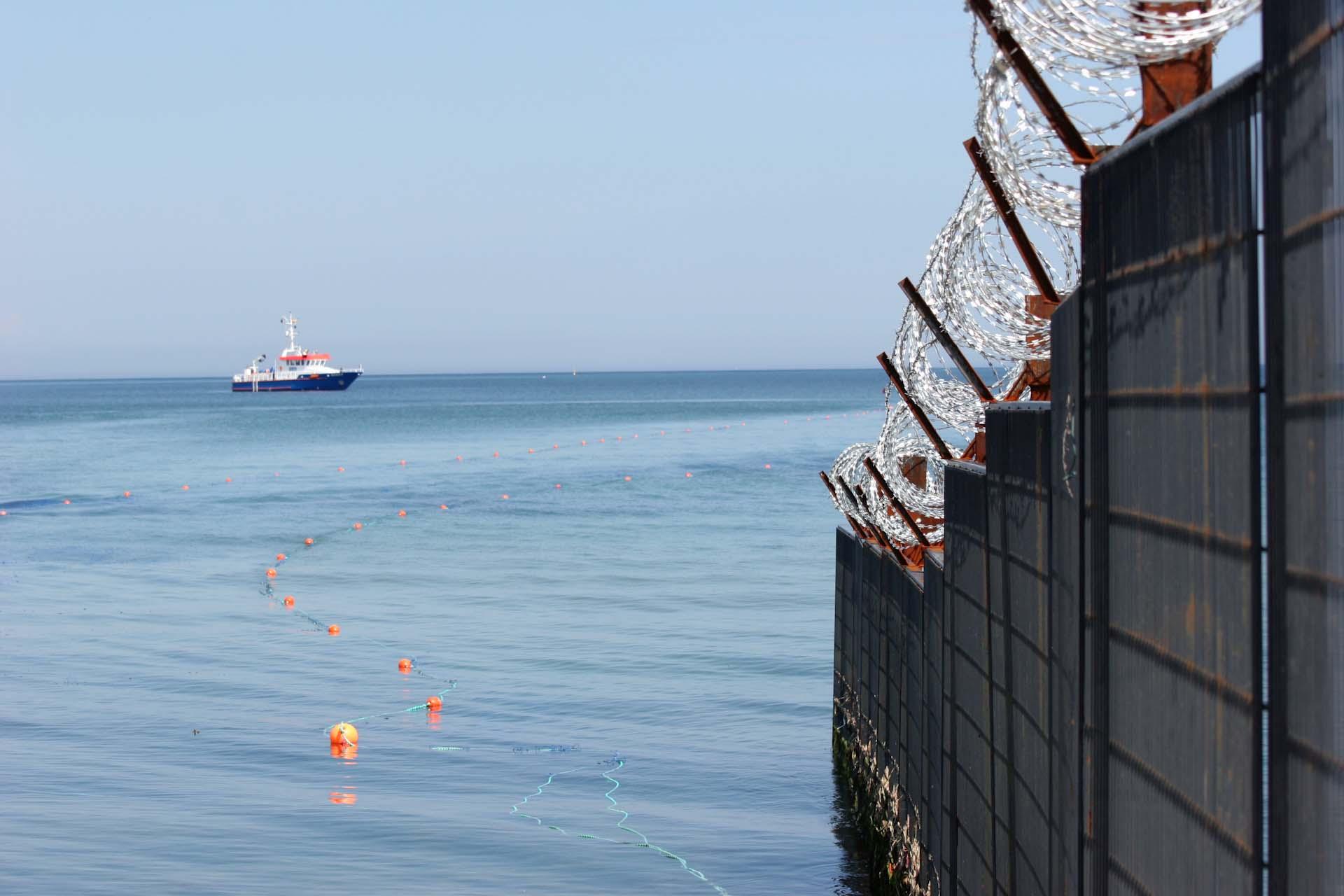 Ein Polizeischiff vor dem Strand von Kühlungsborn. Die Bojen markieren die Netze, die Tauchende Demonstranten verhindern sollen.