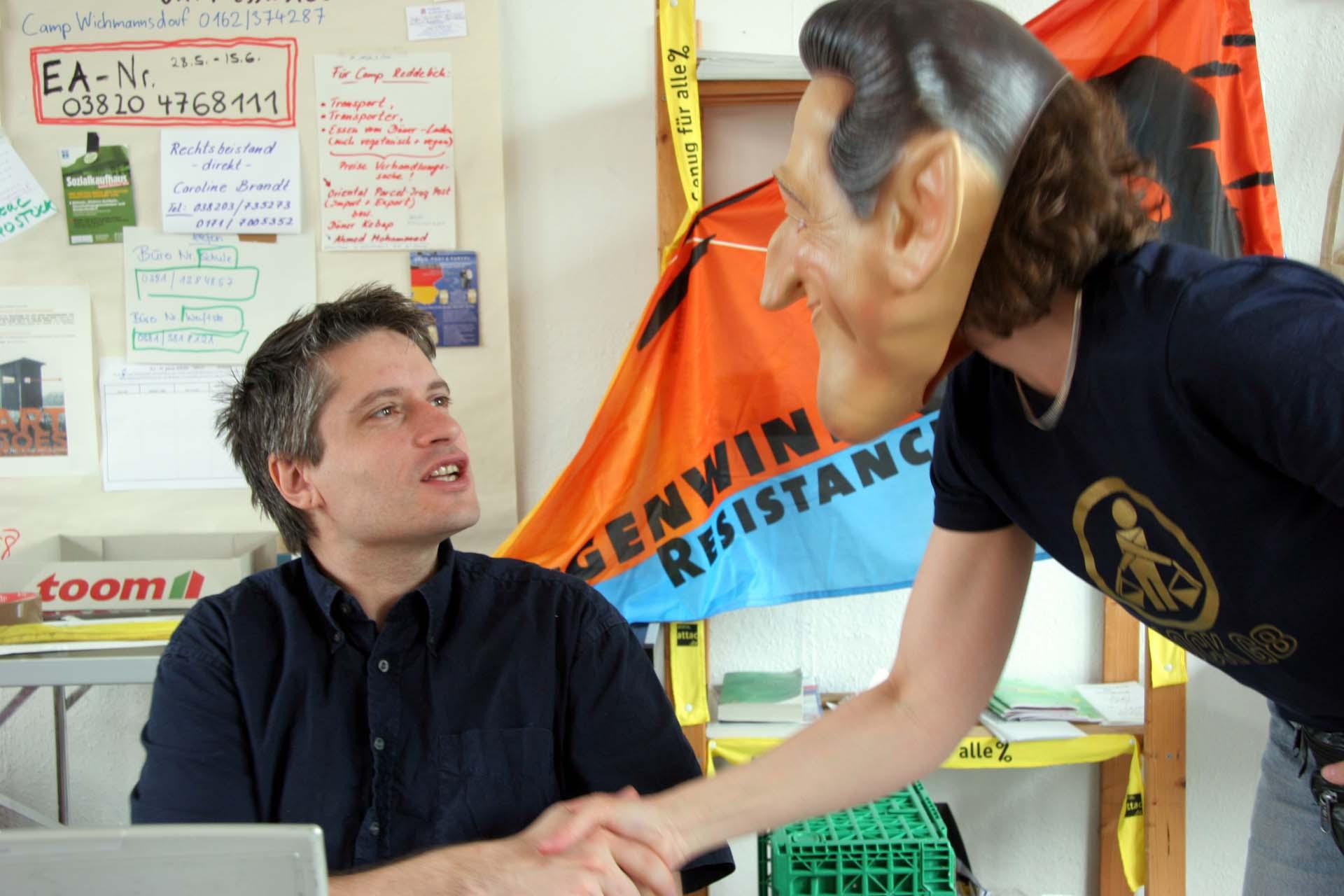 """Sven Giegold vom Attac Koordinierungsrat im Attac Büro des Convergence Center in Rostock schüttelt """"Nicolas Sarkozy"""" die Hand..."""