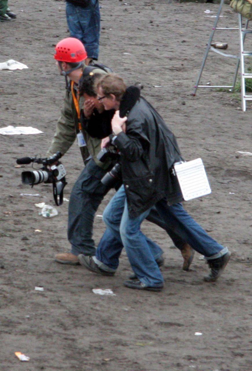 Ein verletzter Journalist wird weggeführt.