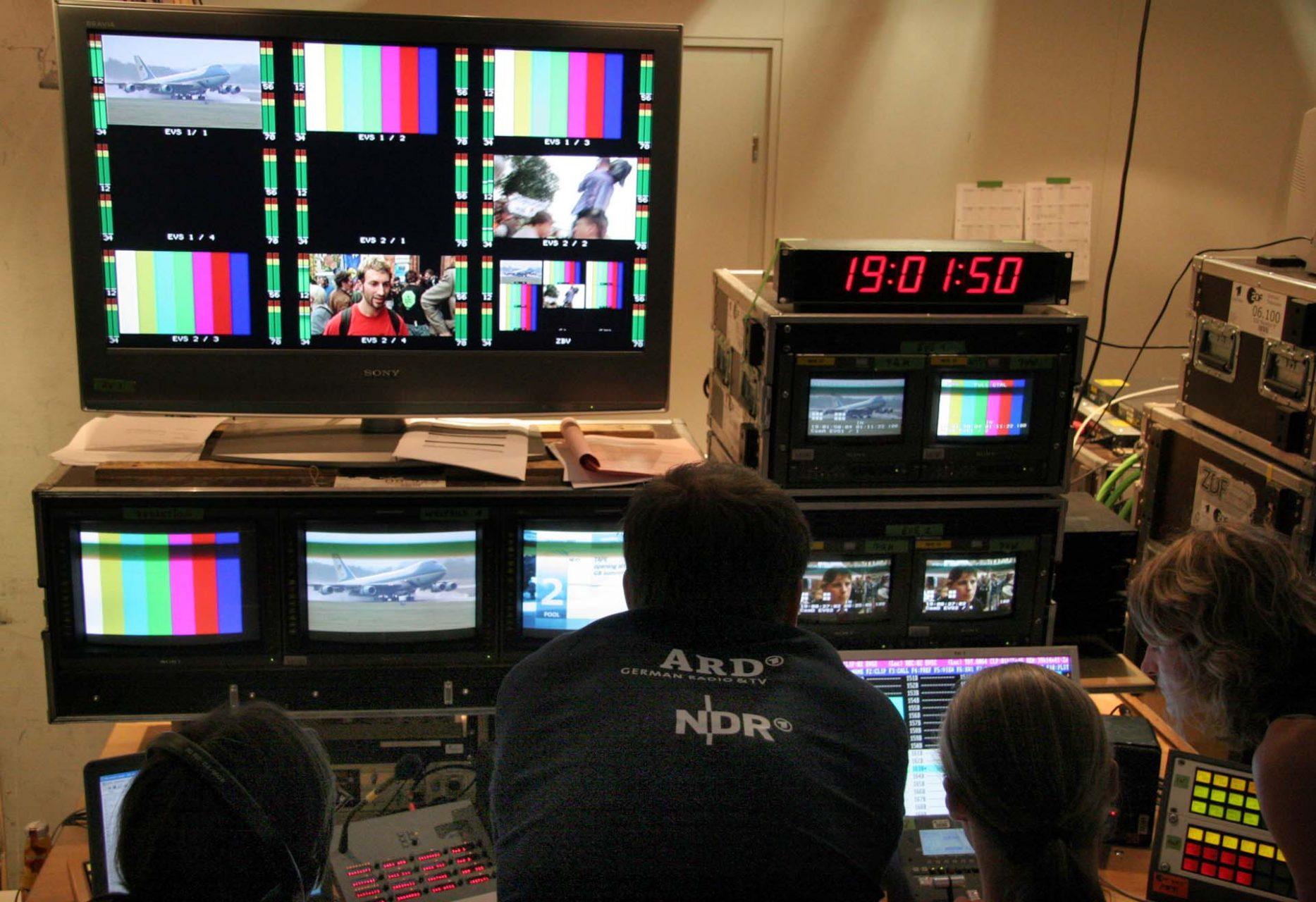 Im Medienzentrum der NDR Screen Welbild. Hier werden die TV Bilder für alle TV Stationen der Welt zusammen- bzw. bereitgestellt. Eben ist die Airforce One mit George Bush gelandet. Auf dem unteren Screen sieht man eine Demo von Globalisierungskritikern und im rechten Bilder von der Demo in der Nähe des Flughafens Laage.