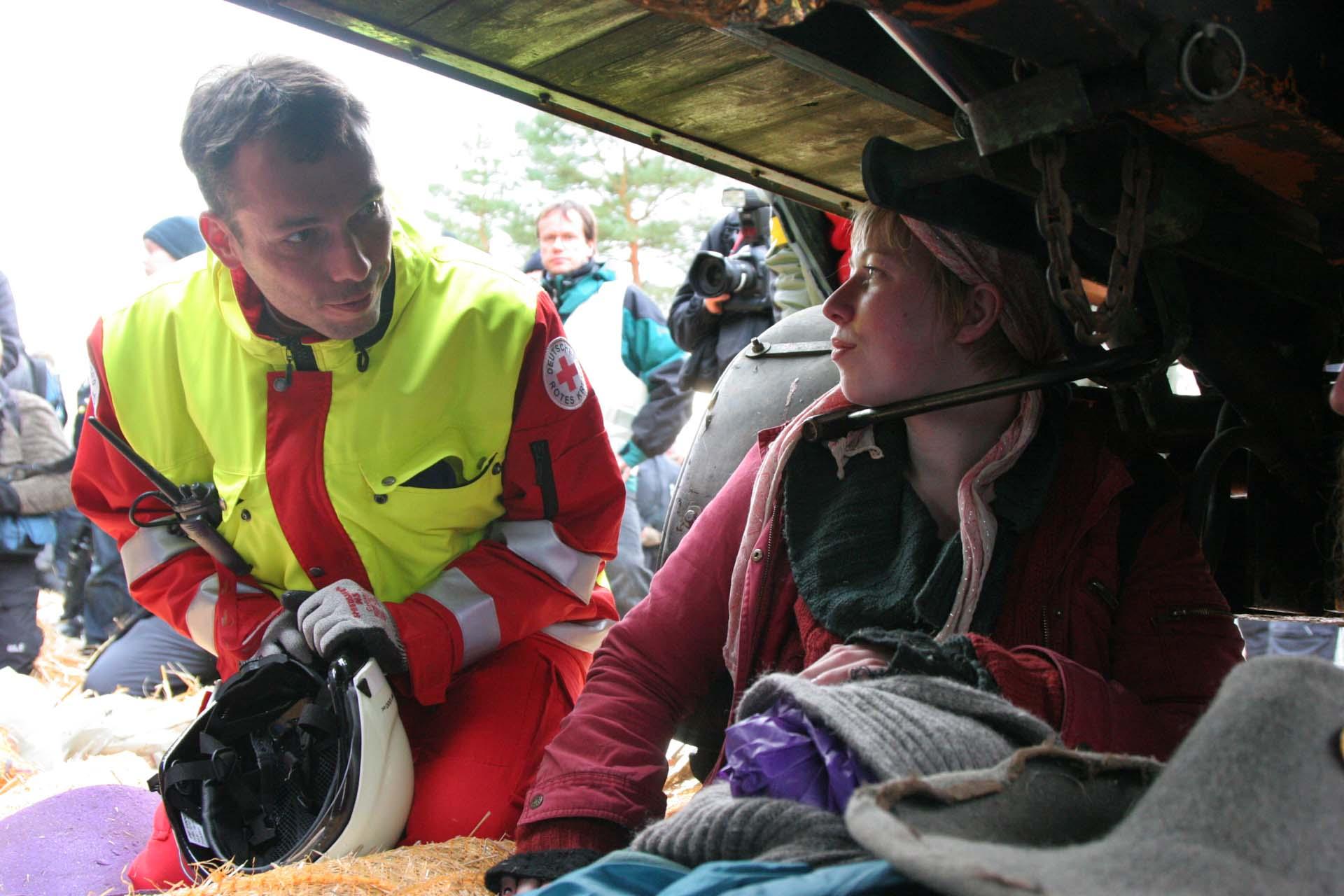 Eine junge Frau hat sich vor dem Zwischenlager mit einem Bügelschloss unter einem Wagen angeschlossen. Es dauert eine Stunde bis Spezialisten das Schloss öffnen können. So lange wird sie von Sanitätern versorgt.