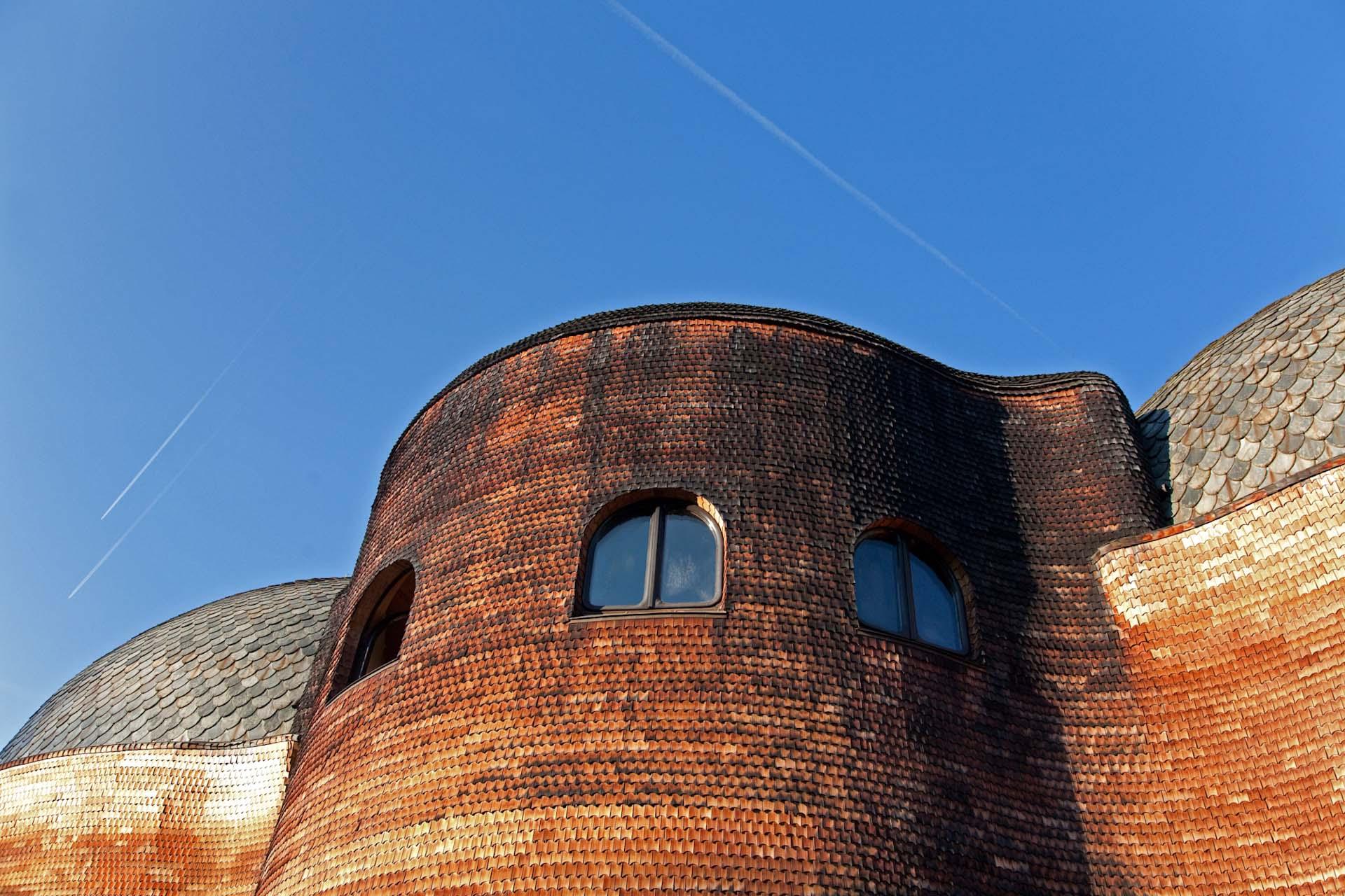 Das hölzerne Glashaus gehört zu den frühen Bauten und verkörpert den Baustil des ersten Goetheanum – dort wurden die Glasfenster geschliffen. Es besteht aus zwei schindelbedeckten Kuppeln, mit einer kleinen Terrasse dazwischen – The wooden Glass House consists of two shingle-covered domes, with a small terrace in between.