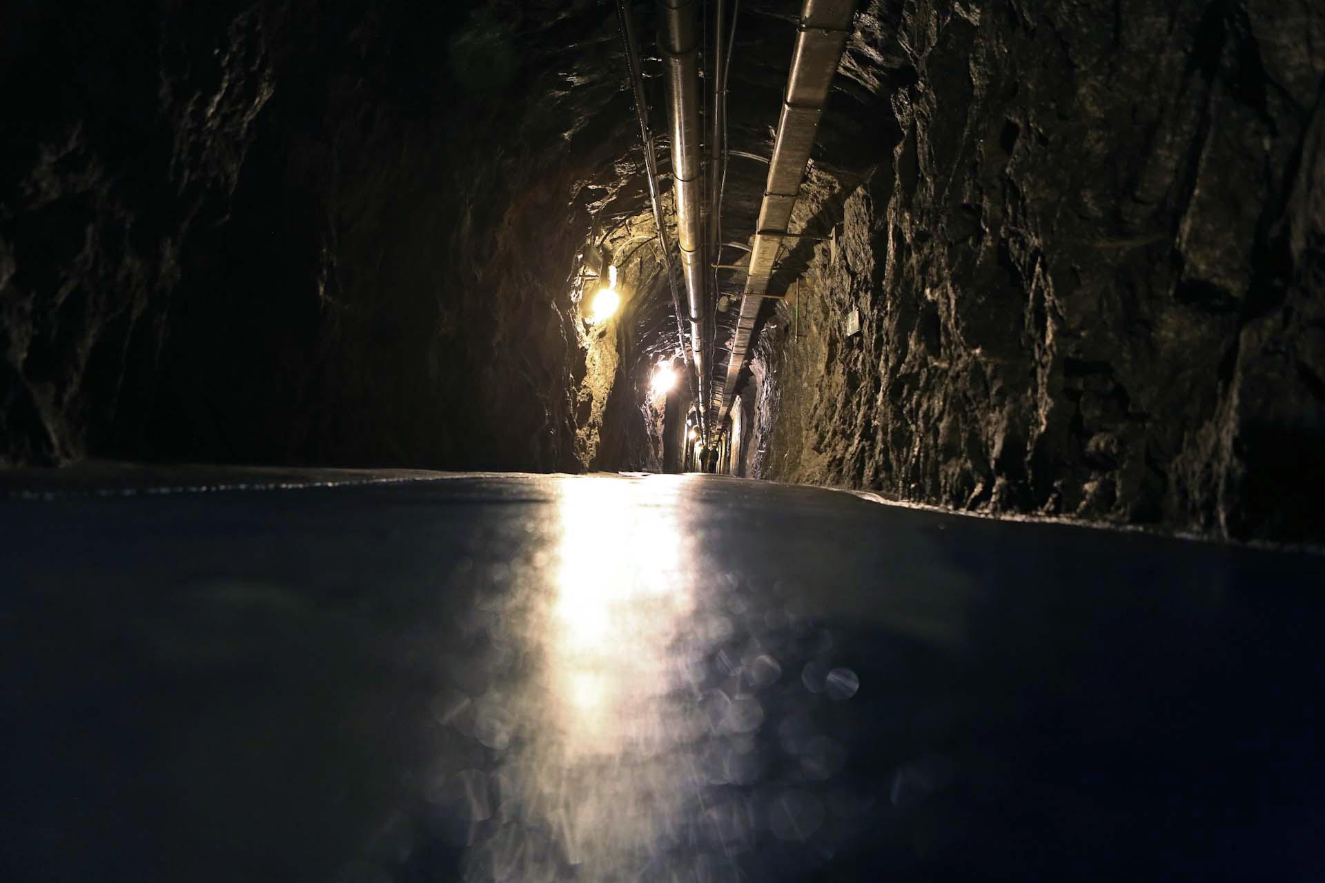 Im Berg ist es feucht und kalt. Es geht schnurgerade durch endlose spärlich beleuchtet Gänge immer tiefer in den Berg hinein, an der Decke befinden sich diverse Versorgungsleitungen.