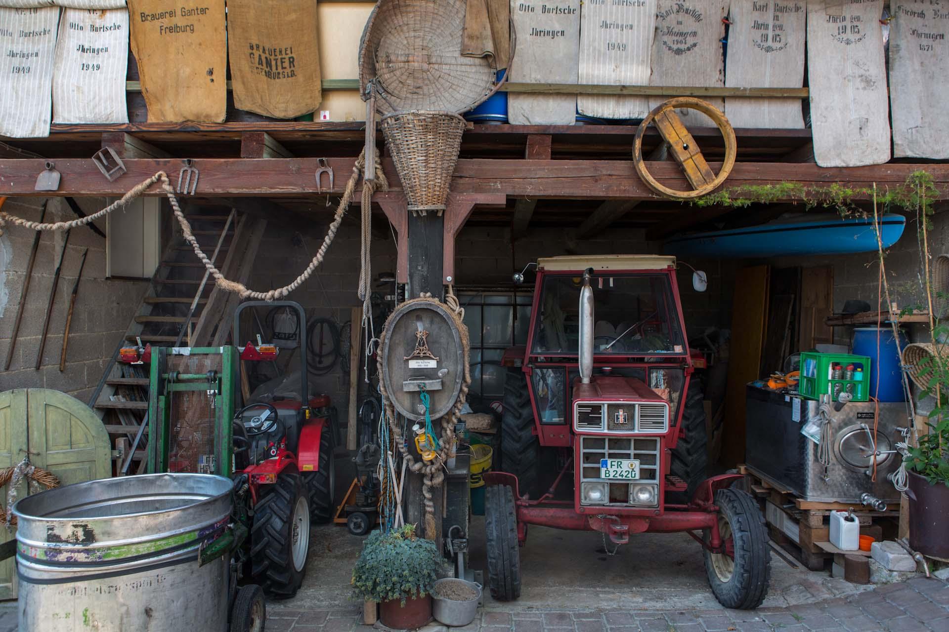 """""""Das große Tor sieht aus wie ein Fass. Wer die Breisachers besuchen will, muss da durch. Ist es offen, ist das wie eine Einladung, sich den Bauerngarten, der oasenartig an das Haus und die ehemaligen Scheunen und Stallungen grenzt, anzusehen, dabei vorbeigehend an altem Winzerwerkzeug, Fuhrwerken, Pferdegeschirren, Fässern und allerhand andere Dekoration. Wo ein Hohlraum entsteht, wird er begrünt, Schuhe oder kaputte Tonschalen auch."""""""