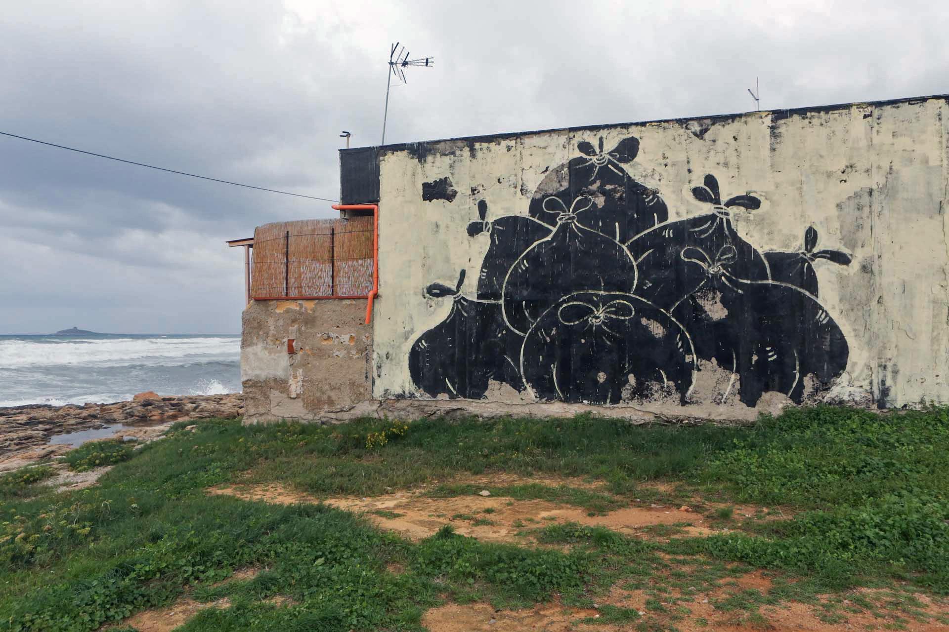 Mural dei Mangiatori di Patate dipinto sulla fiancata di una casa abbandonata.