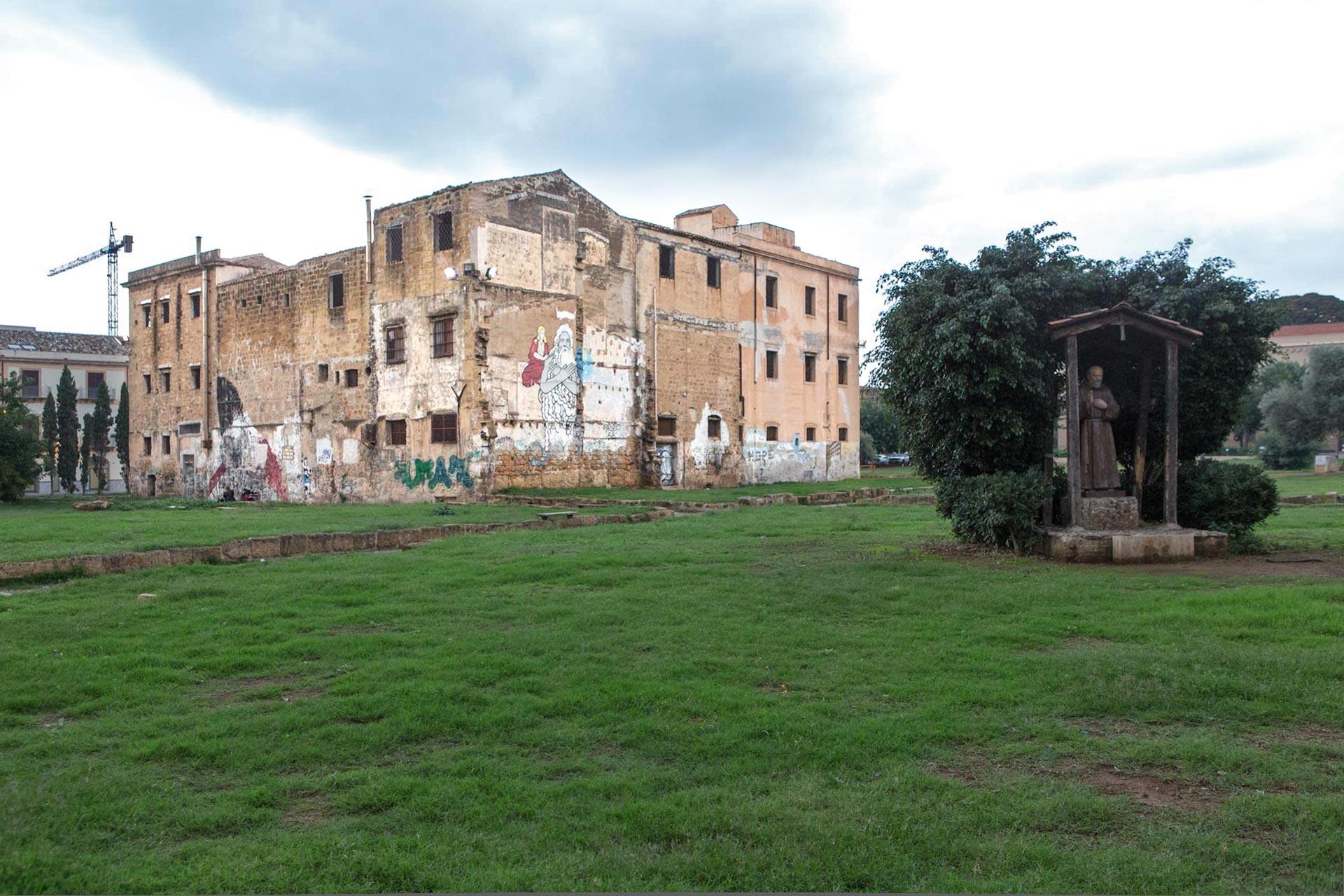 """""""Die Piazza Magione mutet an wie eine moderne Installation, voller unwirklicher Leere zwischen Kriegsruinen und mit EU-Geldern renovierten Palästen, die mit günstigen Airbnb-Tarifen um Kunden werben. Unter einem Olivenbaum steht der Gedenkstein für den ermordeten Antimafia-Staatsanwalt Giovanni Falcone, der wie sein Freund und ebenfalls ermordeter Kollege Paolo Borsellino hier aufwuchs, an den in der benachbarten Via della Vetreria eine kleine Gedenkstätte erinnert. In der Mitte des Platzes thront wie eine Festung ein Kloster, auf dessen Seitenwand ein riesiges Graffito verwittert, das einen schlafenden Papst zeigt: Erschöpft stützt er sein Gesicht auf die Hand und blickt auf die leeren Rasenflächen mit dem Straßenpflaster und den zerstörten Fundamenten der Häuser.""""  Text (Ausschnitt): 'Im Garten der Konzepte' von Petra Reski für DIE ZEIT"""