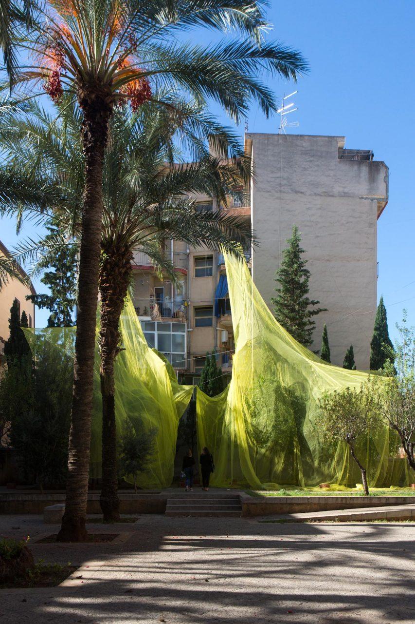 """Giardino dei Giusti – Die Installation des Londoner Kollektivs Cooking Sections bietet eine zeitgemäße Neuinterpretation von offenen Plätzen in der Stadt, quasi Schutzräumen, die dank der Abschattung, den Durchzug der Luftströme erleichtern und so in günstiges Mikroklima erzeugen. Inspiriert wurde das Projekt vom traditionellen Jardinu Pantesco, dem für die Insel Pantelleria typischen, eindimensionalen Garten. In Zusammenarbeit mit Agronomen der Universität Palermo wird der Gesundheitszustand der Bäume überwacht.  Früher bekannt als Lorbeergarten, beherbergte dieser Garten einst einen monumentalen Lorbeerbaum, der 1704 entwurzelt wurde. Heute ist der """"Garten der Rechtschaffenen"""" ein offener Raum, der von den Resten der während des Zweiten Weltkriegs bombardierten Mauern umgeben ist. Ein Raum, der den arabo-normanischen mittelalterlichen Gärten nachempfunden ist, die in städtischen Gebieten angelegt wurden, die verlassen oder von verfallenden Ruinen verschüttet wurden. Im Inneren befinden sich sieben Zitrusbäume."""