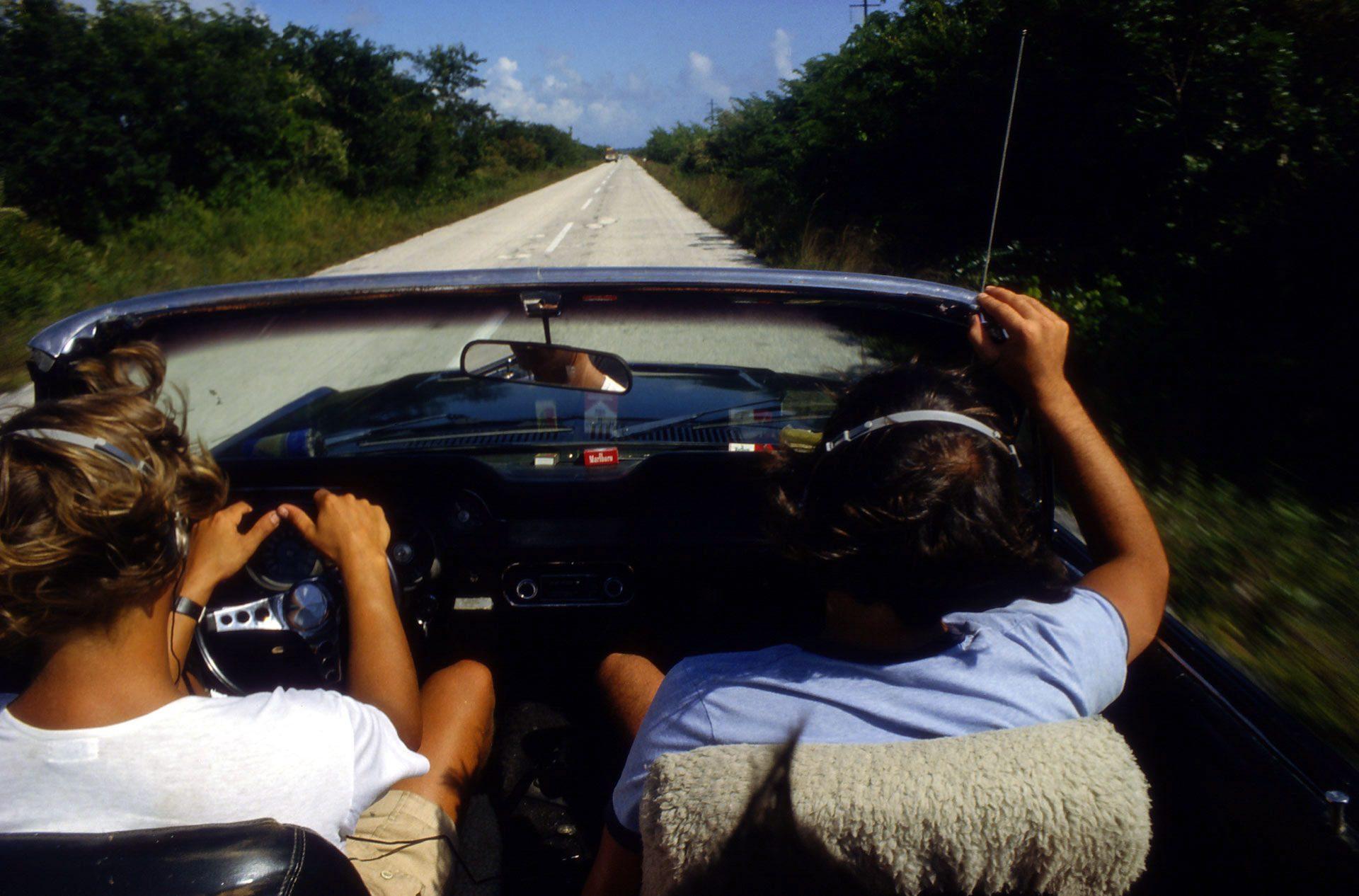 Hippe US-Boys im Ford Mustang Cabrio auf der Straße nach Tulum - Acapulco Gold und Cowboy Zigaretten intus, Musik vom Walkman hörend, der gerade auf den Markt gekommen war – Hip US Boys in Ford Mustang Convertible on the road to Tulum - Inhaling Acapulco Gold and Cowboy Cigarettes, with music from the Walkman who had just come onto the market